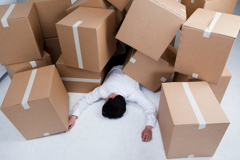 Office Moving Boxes can be overwhelming - photo of a man trapped underneath them