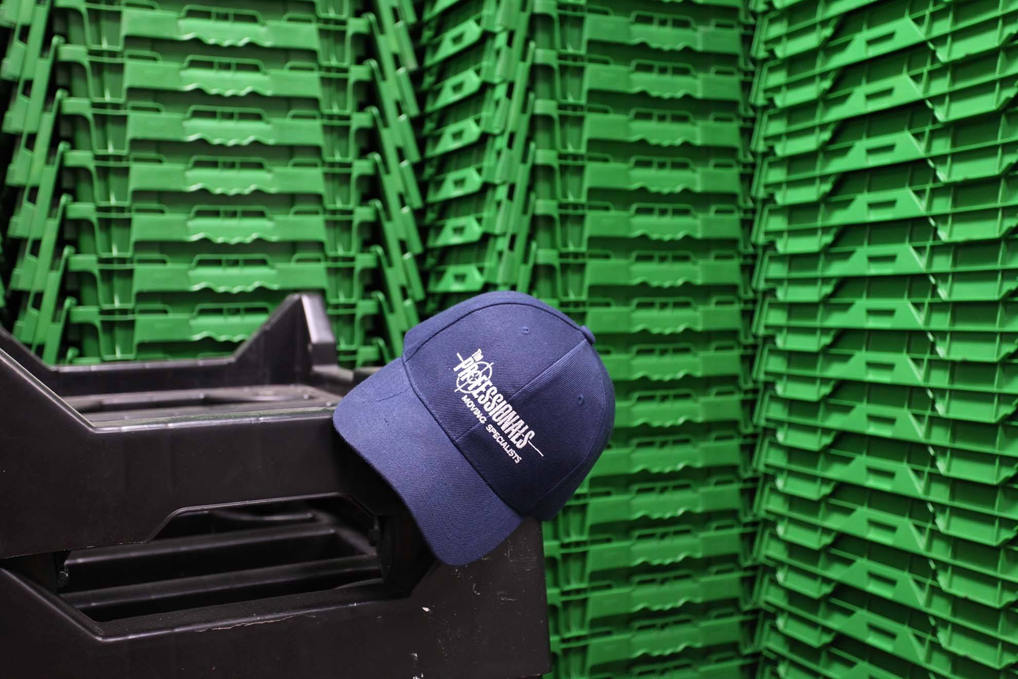 green boxes stacked in front of a moving company hat
