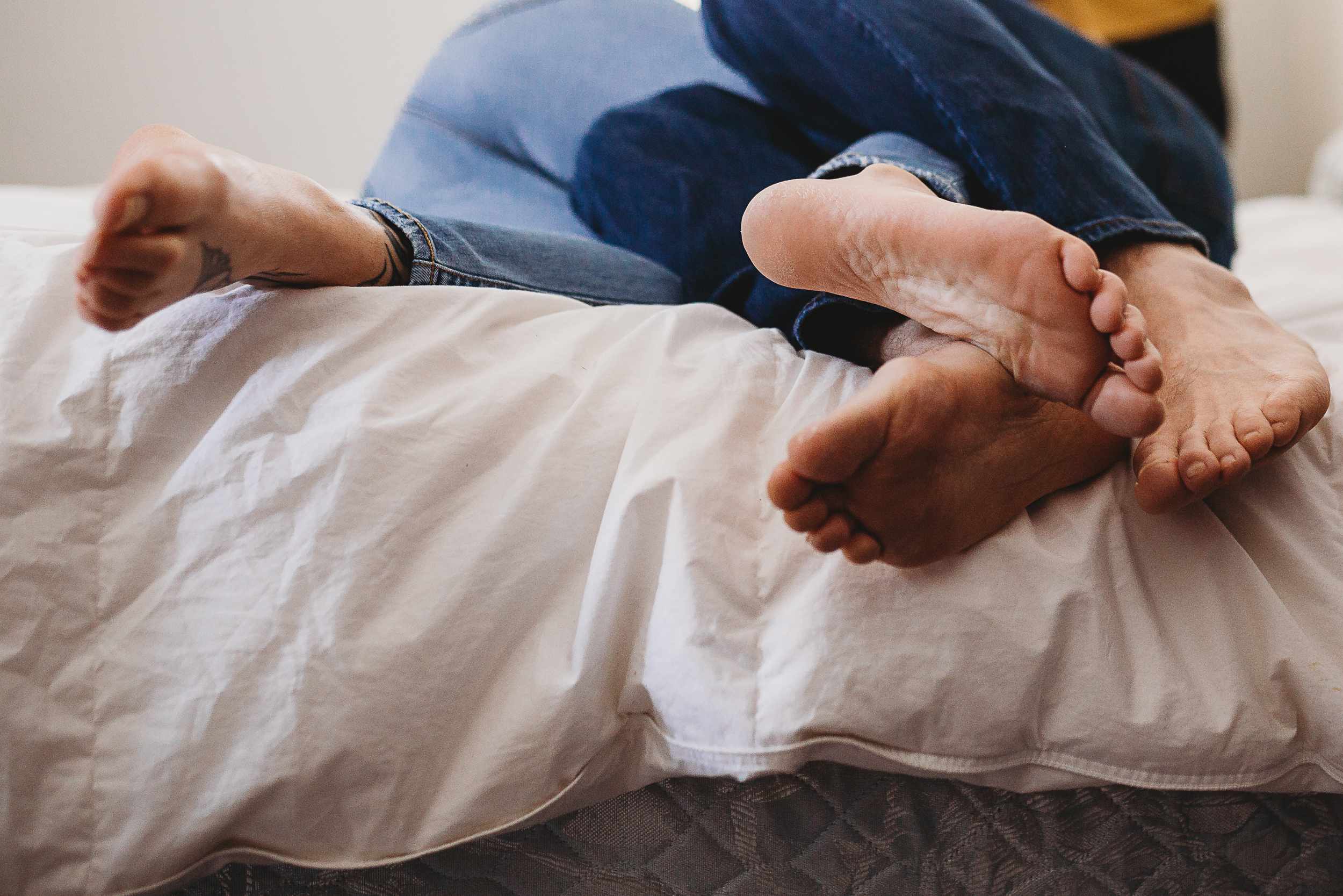 Couple lay on bed and there feet are intertwined during in-home engagement photo session by RaeEllen Photography in New Hampshire