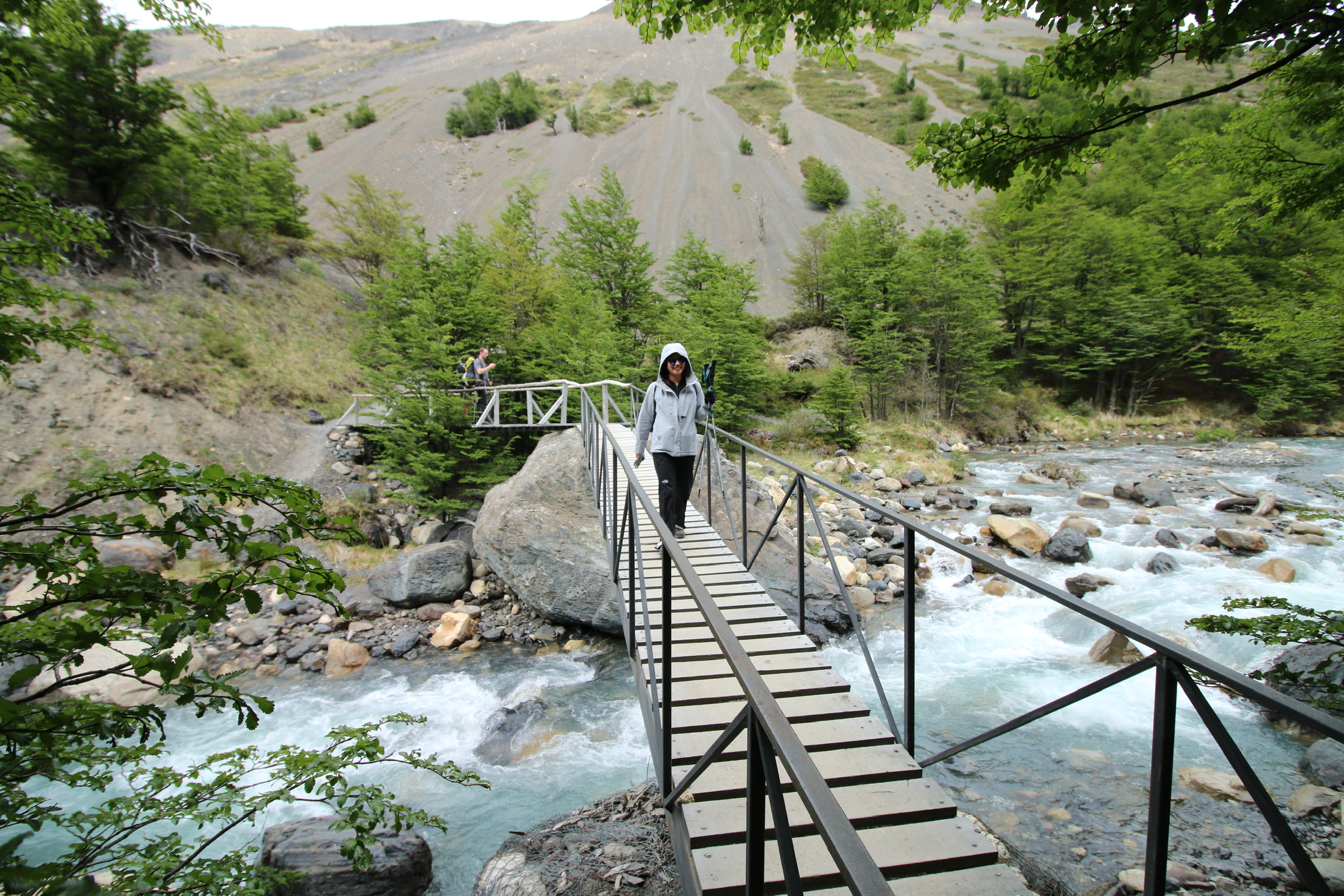 Crossing one of the many bridges in the park over that fresh blue glacial stream.