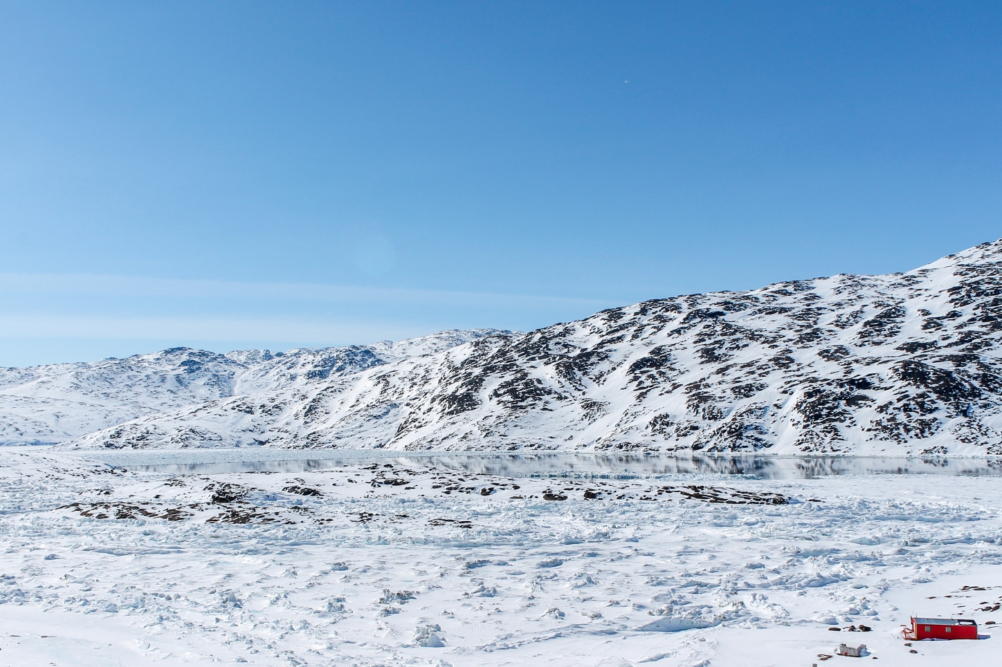 Check out that view! The reflection is a polyna, or area of open water surrounded by sea ice.