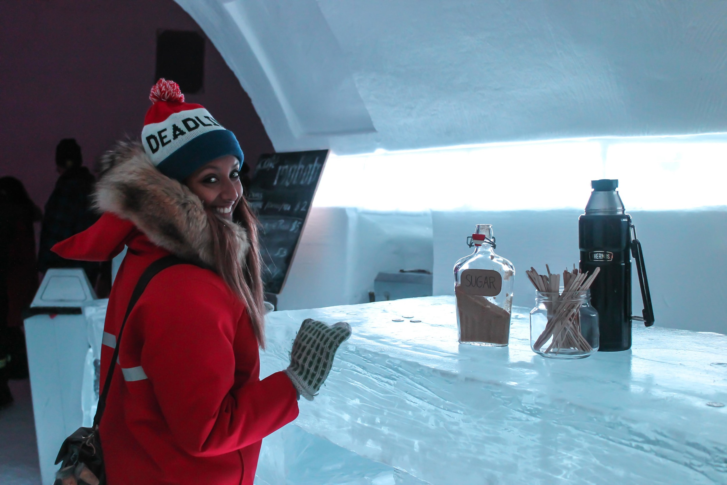 Anubha ordering a hot chocolate at an ice bar inside the Snowking's castle.