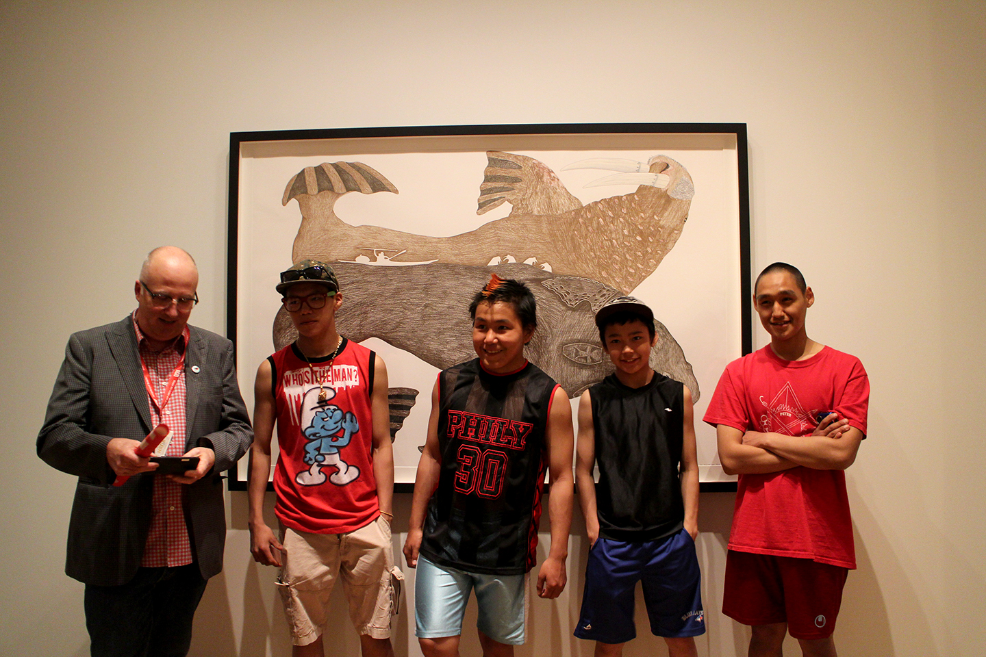 Andrew Hunter from the Art Gallery of Ontario poses with the youth in front of a drawing by Tim Pitsiulak. Photo by Alexa Hatanaka.