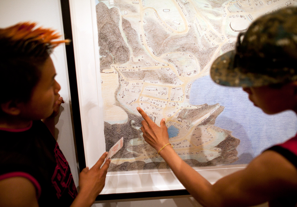 """Audi and Parr locating landmarks on Shuvinai Ashoona's """"Cape Dorset from Above"""" (2012) at the Art Gallery of Ontario. Photo by Tobin Grimshaw."""