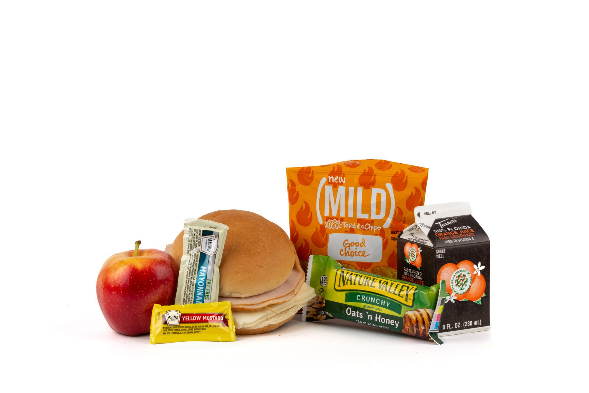 MK08 - Fresh Turkey / Swiss  Sliced Turkey Breast /Swiss On Wheat Bun Chip Tortilla Taco Bell Mild Apple Fuji 100 Mustard Packet Mayonnaise Packet Fatfree Dressing Granola Bar Oats and Honey Orange Juice