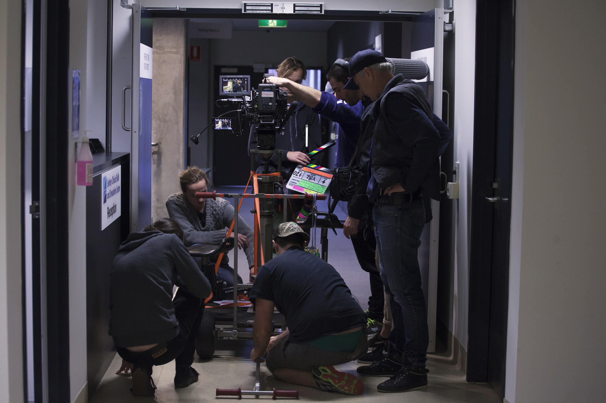 Our grips department responsible for making sure the camera moves without any problems. The crew here are securing a dolly in this picture before it is about to be run down the hallway.