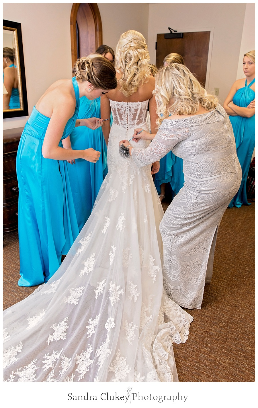 Mom helping bride with final touches on dress