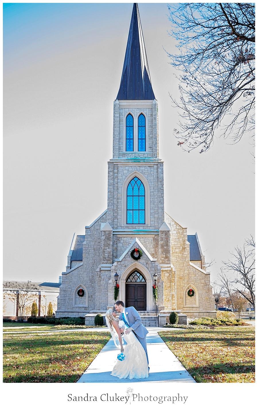 Groom dips bride in front of Chapel