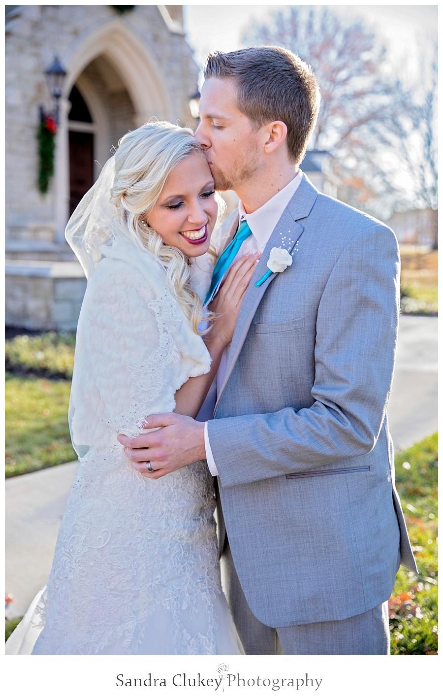 Groom kisses Bride in front of Chapel