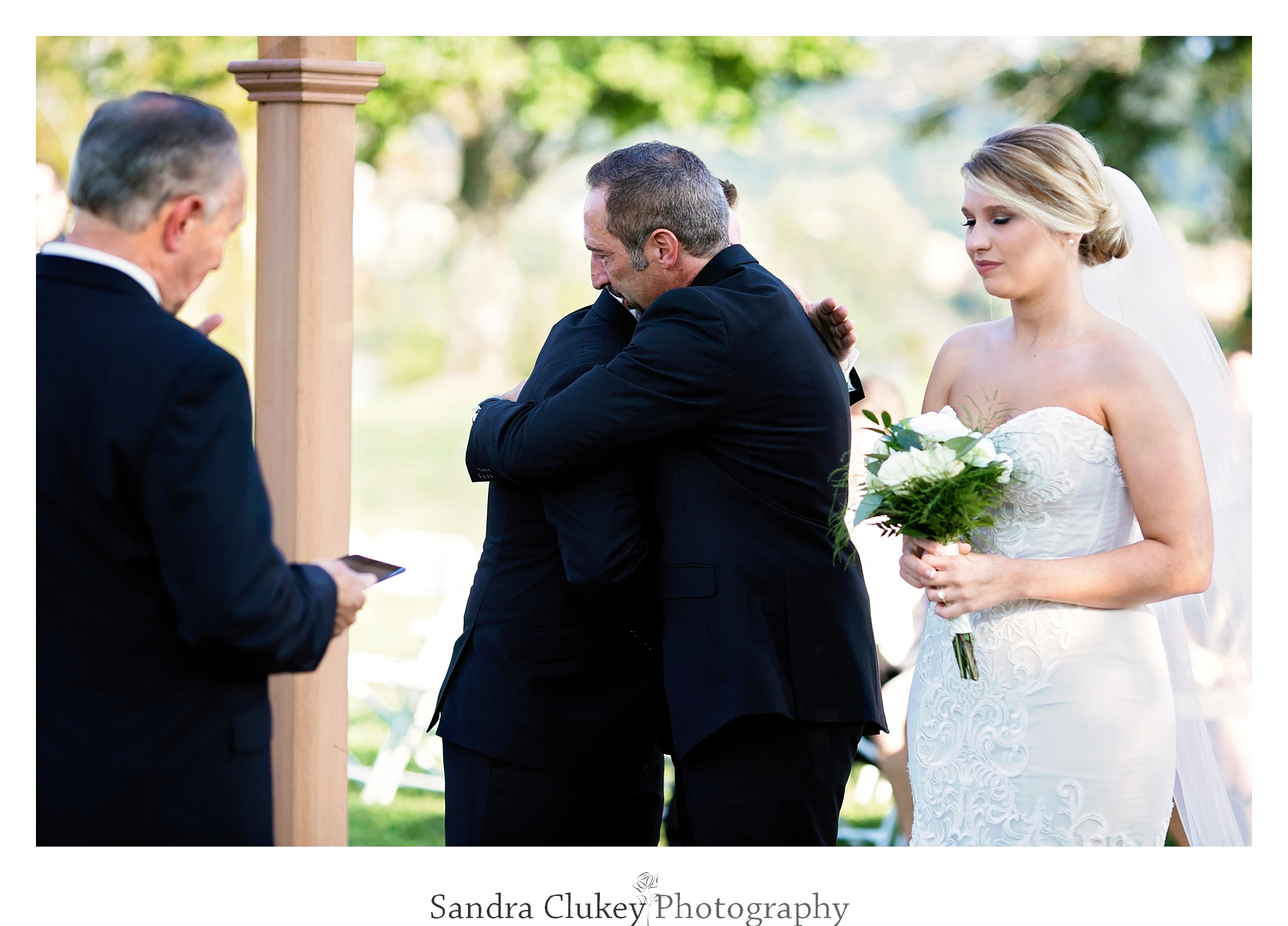 Father of the bride hugs groom at Tennessee RiverPlace, Chattanooga TN
