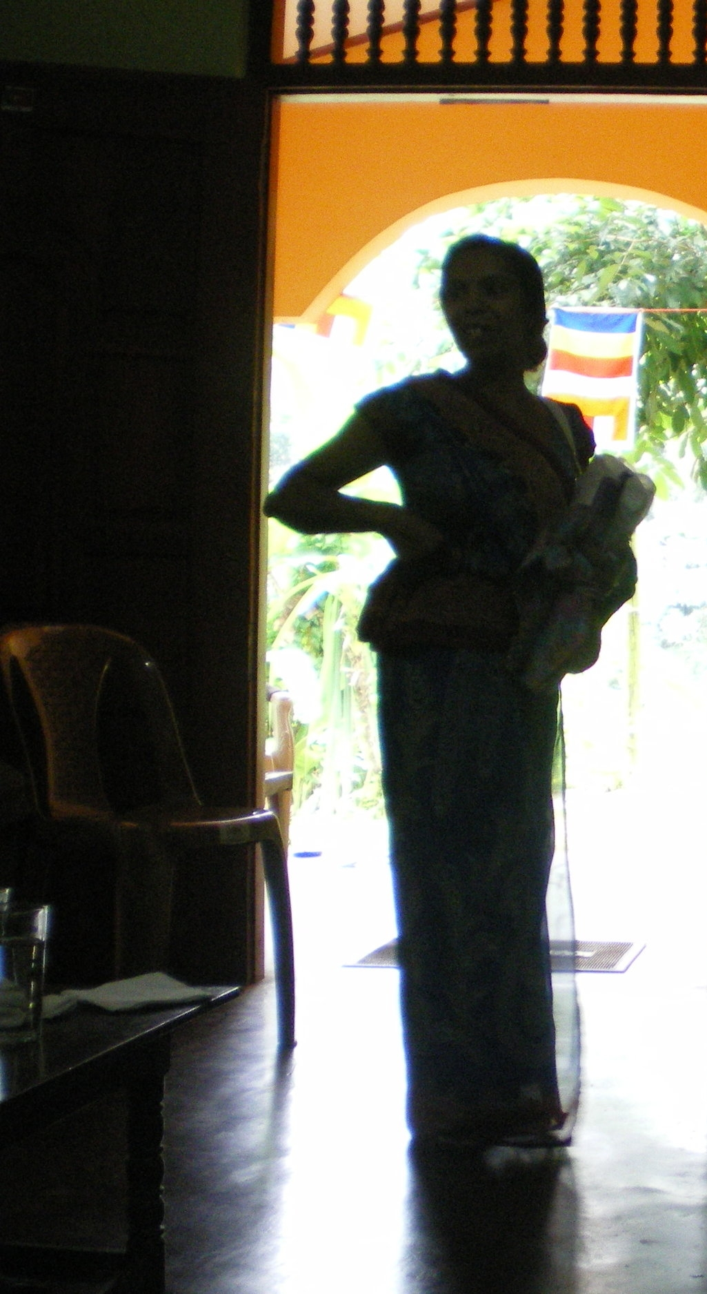 Silhouette of a woman standing at the doorway of a microborrowers group meeting