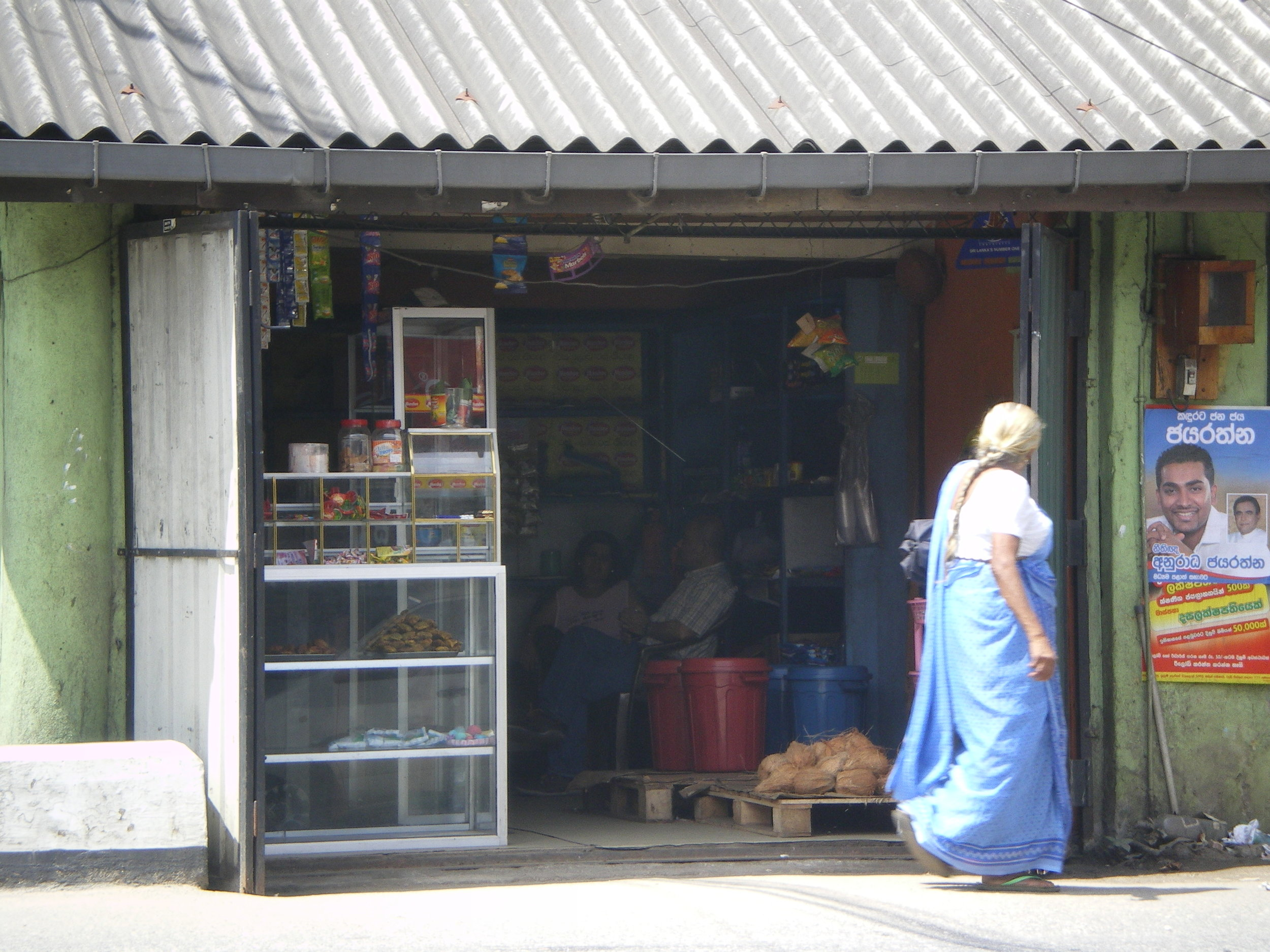 A woman wanders past a market stall started with a microfinance loan