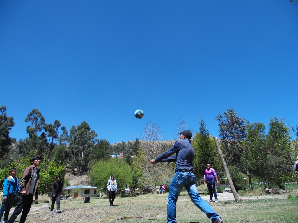 The students playing volleyball on the huge field in Achocalla.