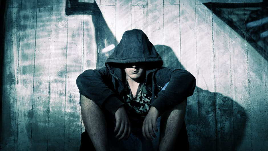 man sitting with hoodie on