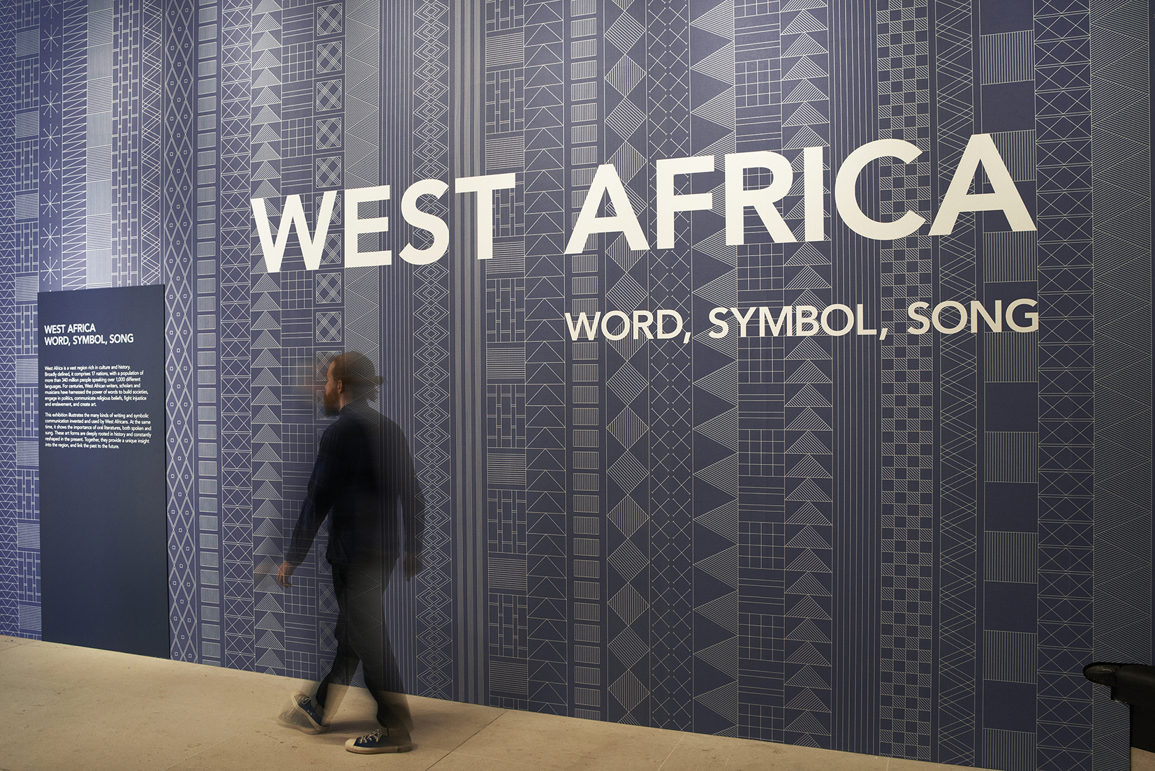 West Africa   Exhibition design, British Library, 2015   An exhibition of literature and music that traces West Africa's history from the great African empires of the Middle Ages to the cultural dynamism of West Africa today.  Extensive research on West Africa symbolism, allowed the creation of a meaningful design system. Patterns are created from vertical lines of symbols; each symbol carrying a meaning that reflects the content of the section. Colours were carefully studied to help the visitor to navigate the space and reflect the exhibition topic without becoming a pastiche.  Project completed with Plaid London Photography: Courtesy of Plaid London