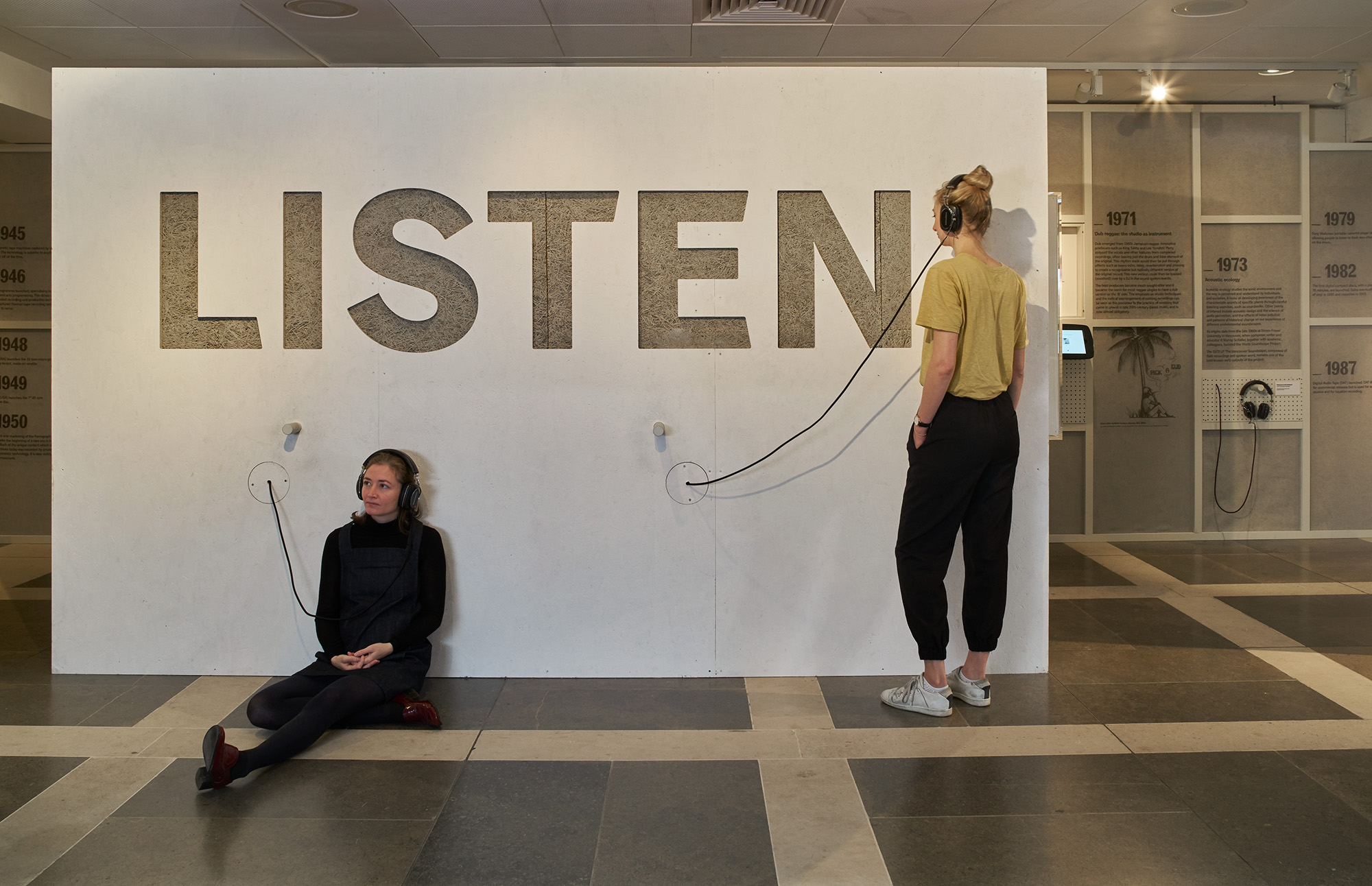 Listen, 140 years of recorded sound   Exhibition design, British Library, 2017   Displaying the extensive British Library's sound archive, this exhibition explores the story of sound recording and radio broadcasting, and the impact each had on society in the last 140 years.  On a 20m sound proof wall, a timeline showcases various media ranging from objects, to audio displays and images. The graphics printed on a transparent voile allow visitors to discover the insulation material at the back.  People are also invited to sit within specially created listening booths that surround the showcases. A focus on providing smaller audio environments within a larger collective space aims to create a feeling of listening as a way of bringing people together through shared engagement.  Project completed with Plaid London