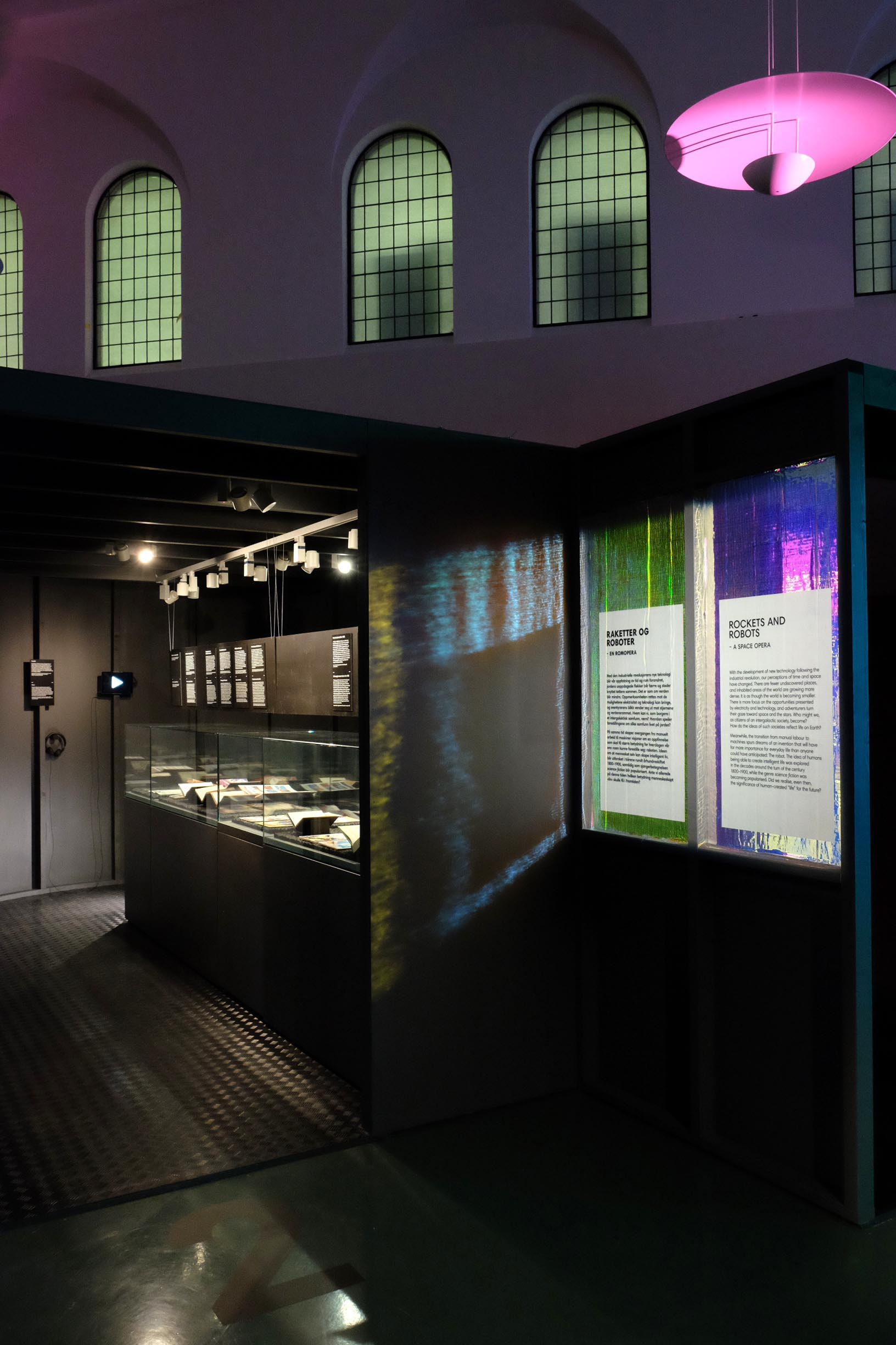 Science Fiction   Exhibition design, National Library Oslo, 2018   In a time where the magic of movies like Blade Runner has to compete with the realism of the technology laboratories of Silicon Valley, the National Library of Norway debates and depicts the fantastic futures of the past and present.  The graphic approach experiments with innovative materials in unexpected combinations. Dichroic film overlays metallic isolation material to create a wide spectrum of moving colours and light reflections on the 3D structure.  Project completed with Plaid London