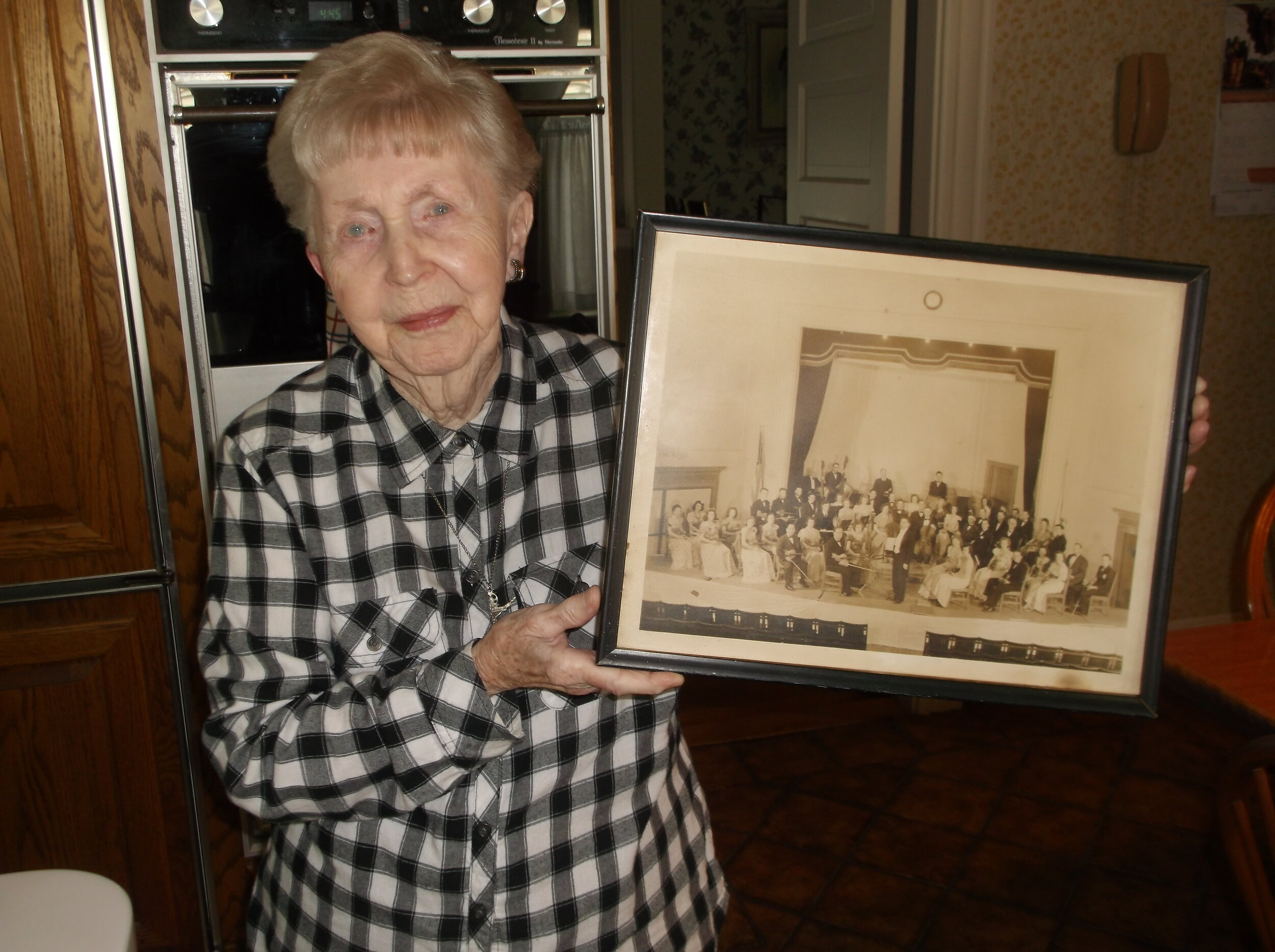 Frances holding a picture of the Lowell Philharmonic taken around 1938. Her father is sitting right behind the concert master (the violinist sitting immediately to the left of the conductor).
