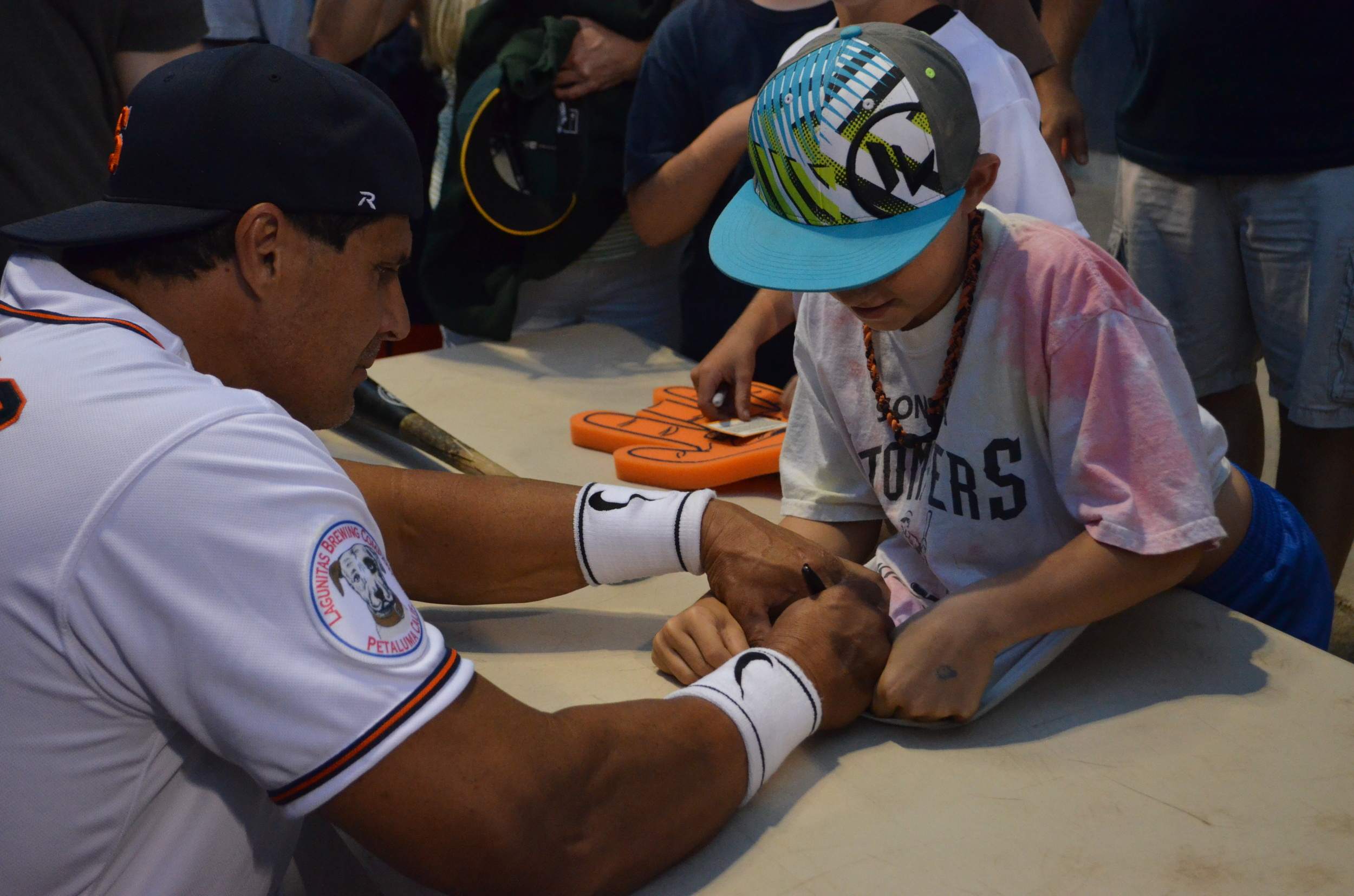 Jose Canseco signs an autograph for a young fan at Arnold Field.   James Toy III/Sonoma Stompers