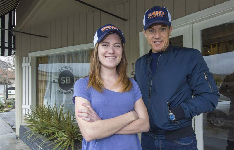 Kelsey Minigan and Jon Sebastiani pose in their new Stompers Baseball caps in front of the Sonoma Brands office on East Napa Street in downtown Sonoma, Calif.  Photo courtesy Robbi Pengelly/Sonoma Index-Tribune .
