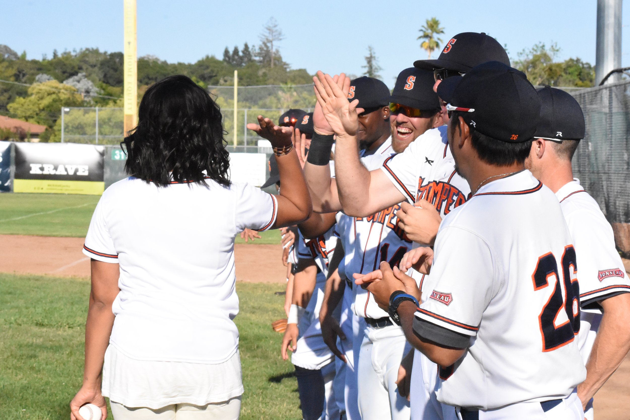 Author and professional chef Ayesha Curry (left) high fives the Sonoma Stompers after throwing the first pitch at Peoples Home Equity Ballpark at Arnold Field. (James W. Toy III / Sonoma Stompers)