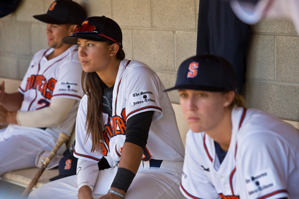 Kelsie Whitmore (center) and Stacy Piagno (right) sit in the dugout at Peoples Home Equity Ballpark at Arnold Field during the Stompers' 2016 Championship season. (James W. Toy III / Sonoma Stompers)