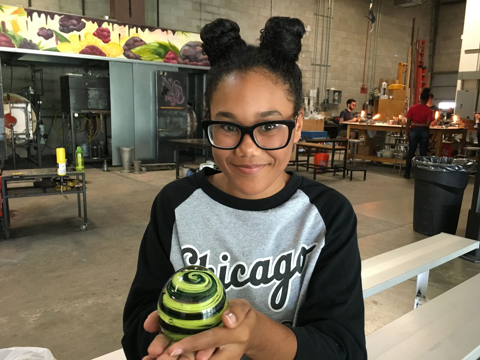 A teen from CYC-Fellowship House poses with her glass paperweight.
