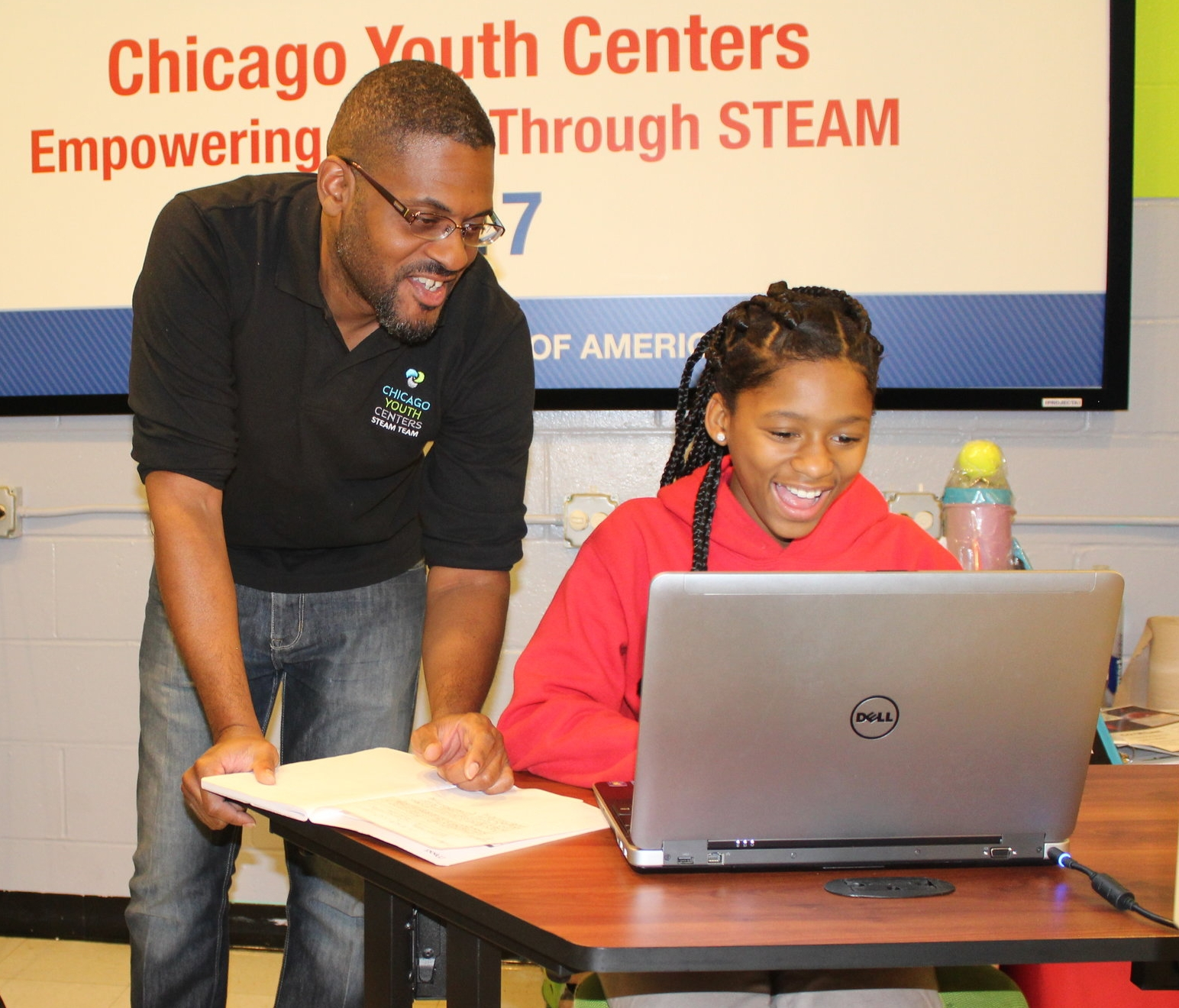 CYC STEM program manager Steven Willis works with a GEMS club member on a rocket project.