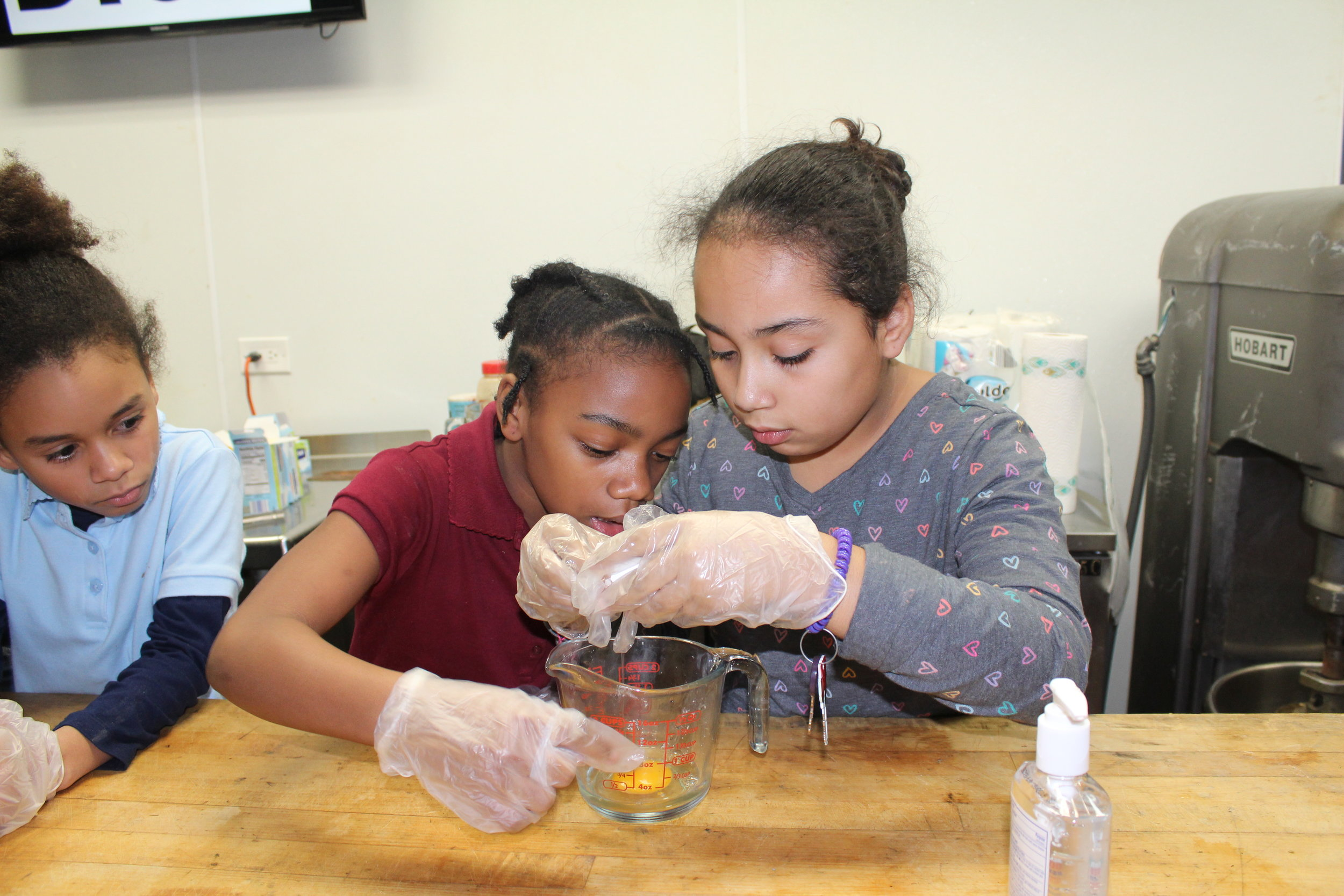 CYC GEMS club member Analiz, right, cracks an egg open during a recent field trip to an industrial kitchen in Chicago. The girls learned about the science that goes into baking.