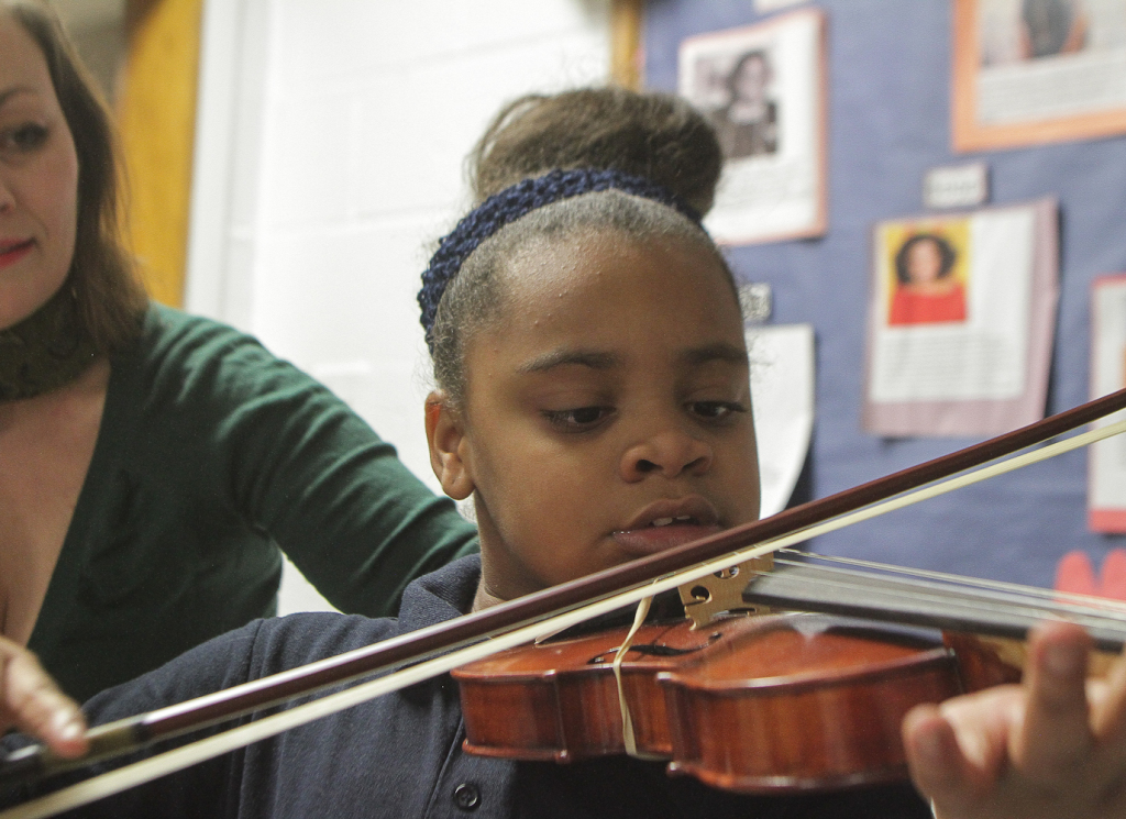 Instructor Elisabeth Johnson watches as India Mabon, 9, goes thru a violin exercise Tuesday at the Crown Center in South Shore. The students are working on different rhythms. | Leslie Adkins/For the Sun-Times