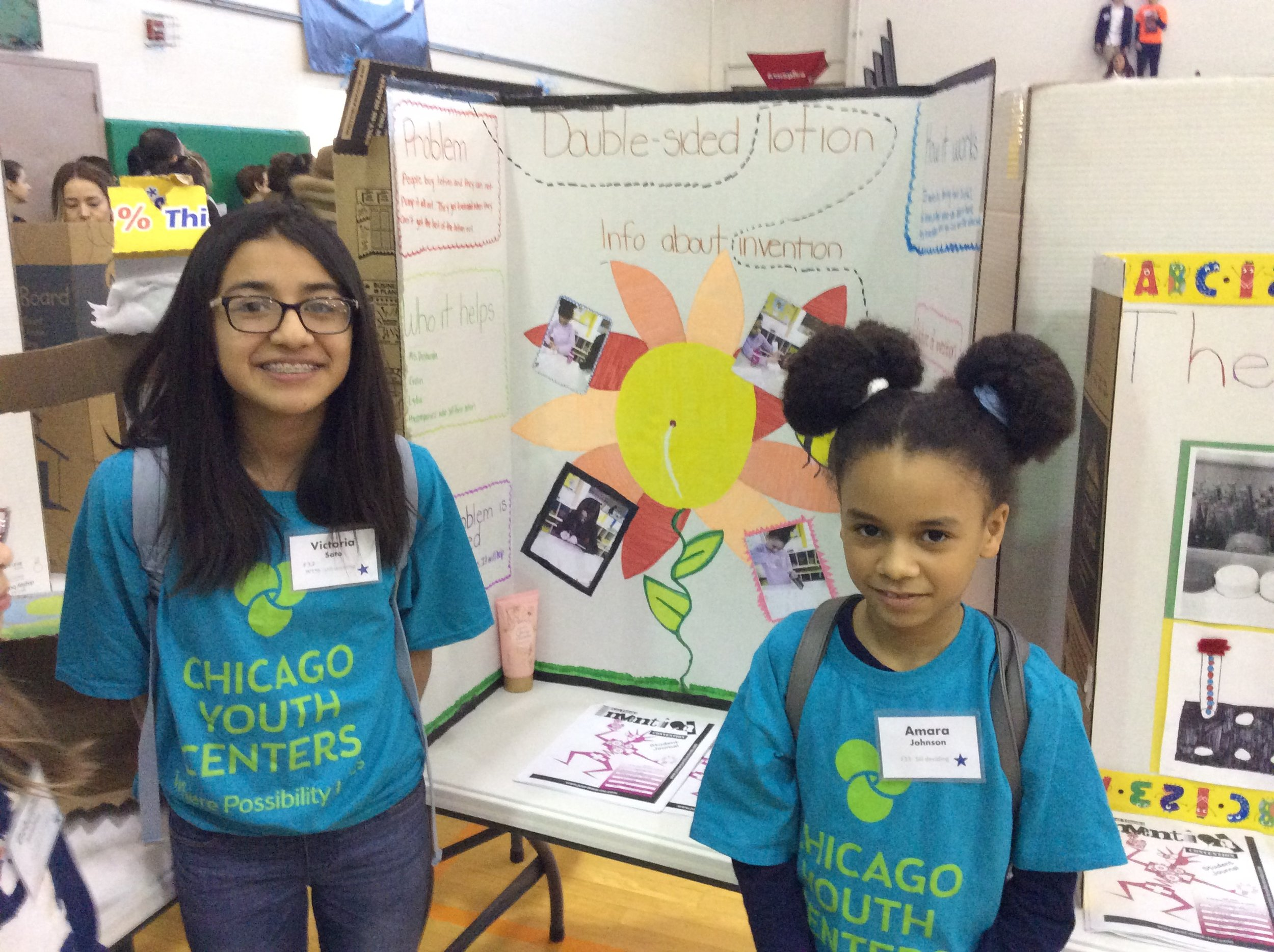 Victoria and Amara, CYC-Fellowship students, pose in front of their presentation at the Chicago Student Invention Convention.