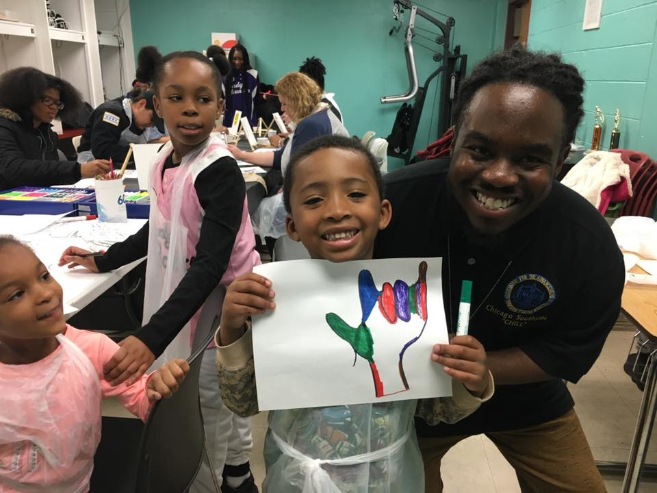 """CYC youth worker Devin Swift-Bailey poses with a child and his interpretation of peace: the sign language phrase for """"I love you."""""""