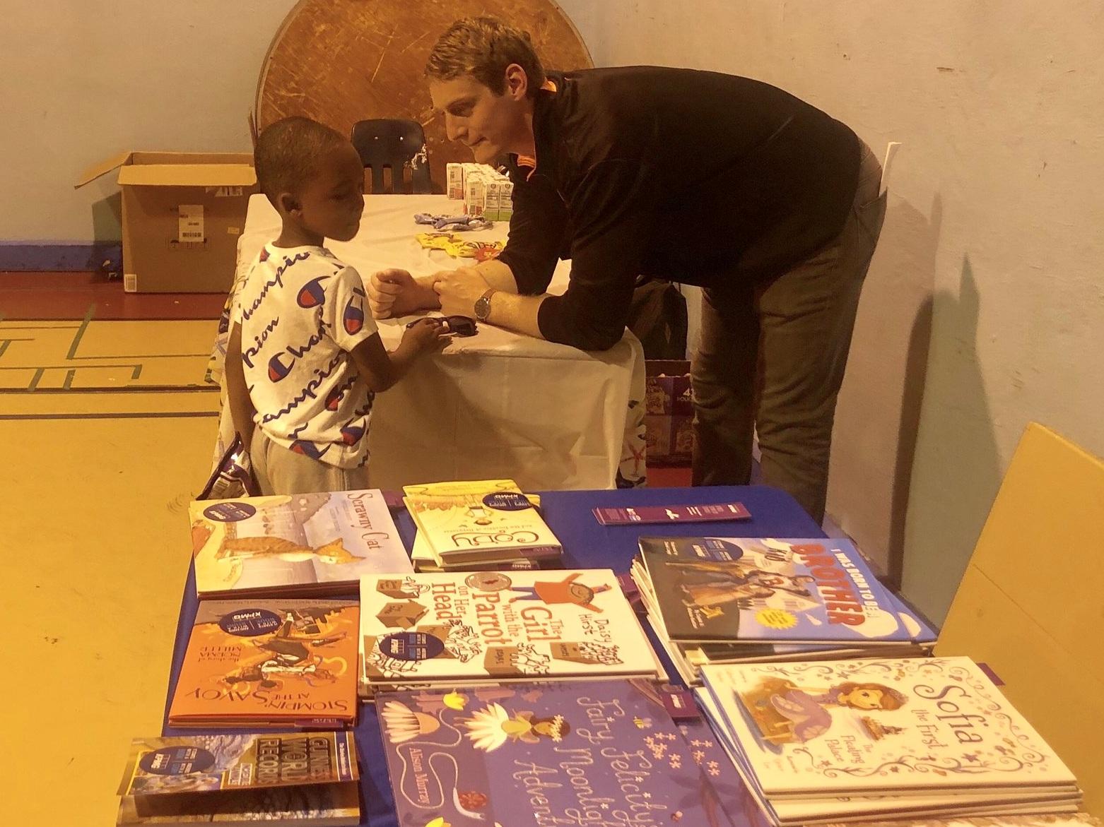 a kpmg employee helps a cyc child pick a new book.
