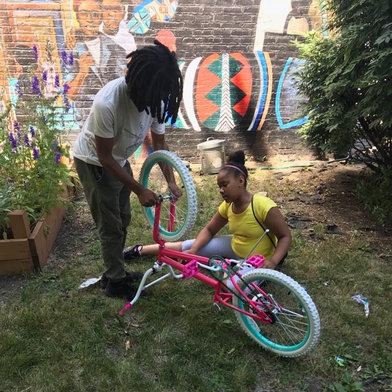 CYC teens work on assembling a bike.
