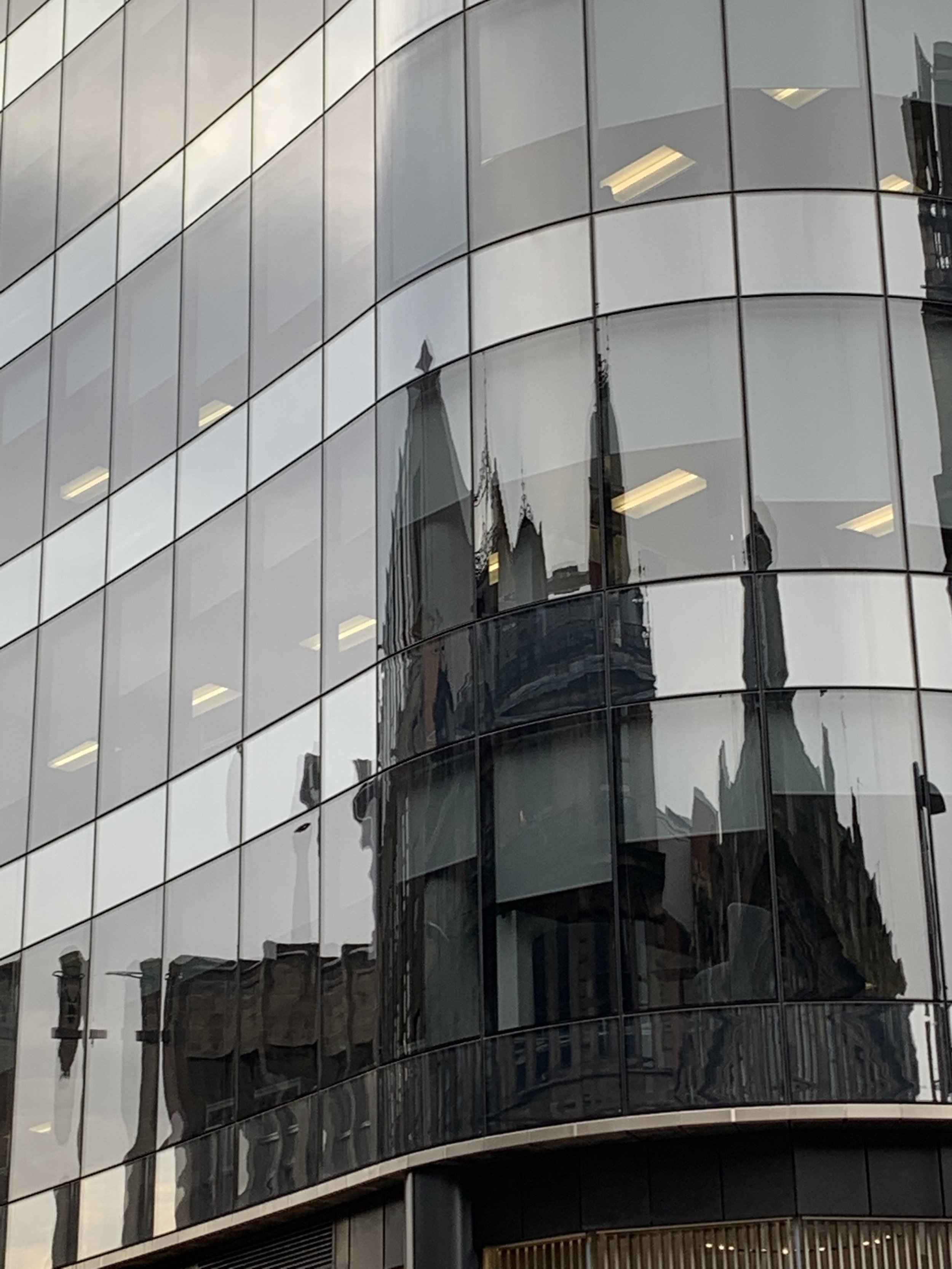 Ancient architecture reflected in modern windows. Glasgow, Scotland