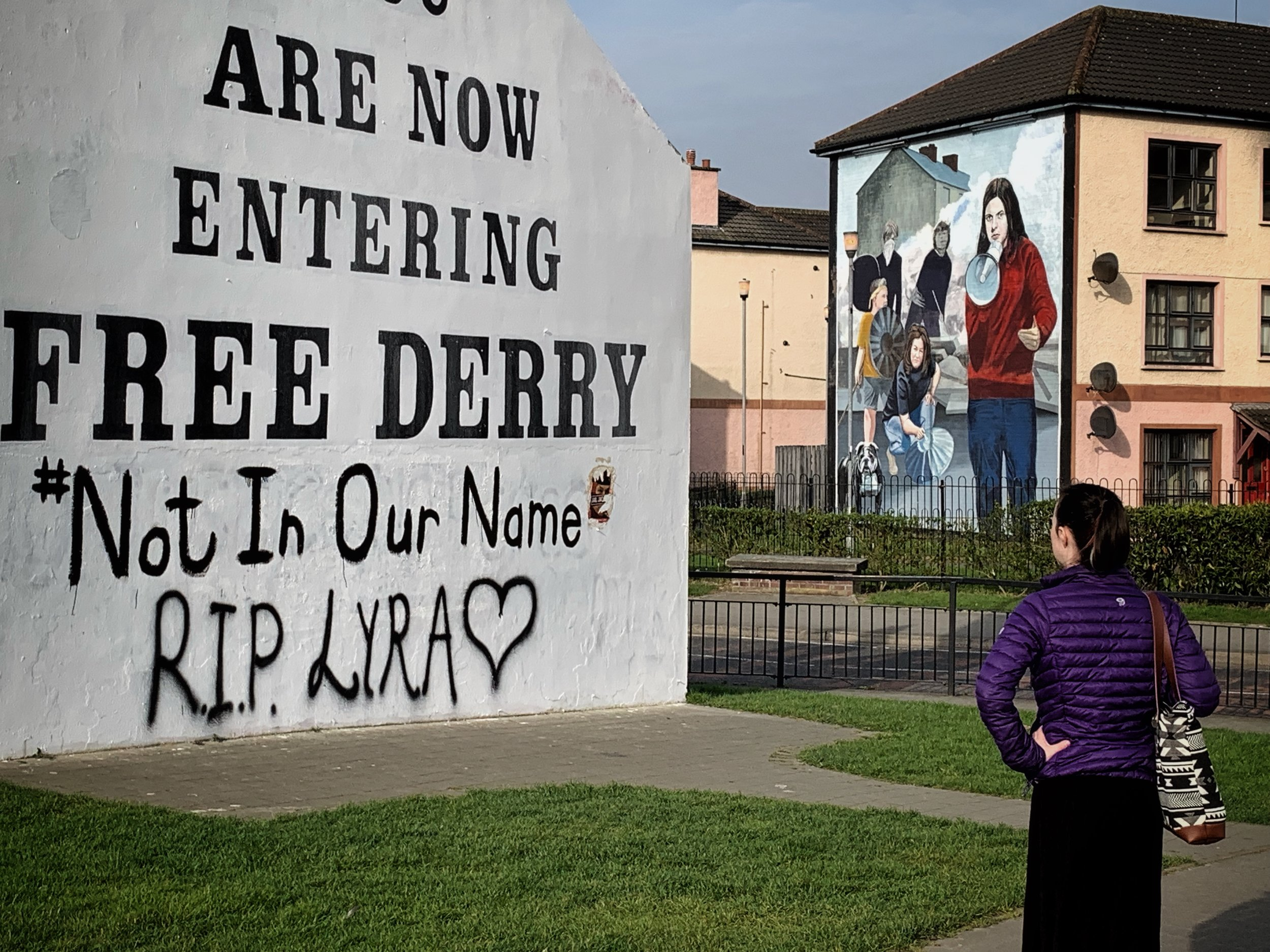 Famous landmark, Free Derry monument, with new graffiti commemorating journalist Lyra McKee, killed April 18, 2019. My daughter reflecting on the words. Derry, N. Ireland. photo by anne richardson.
