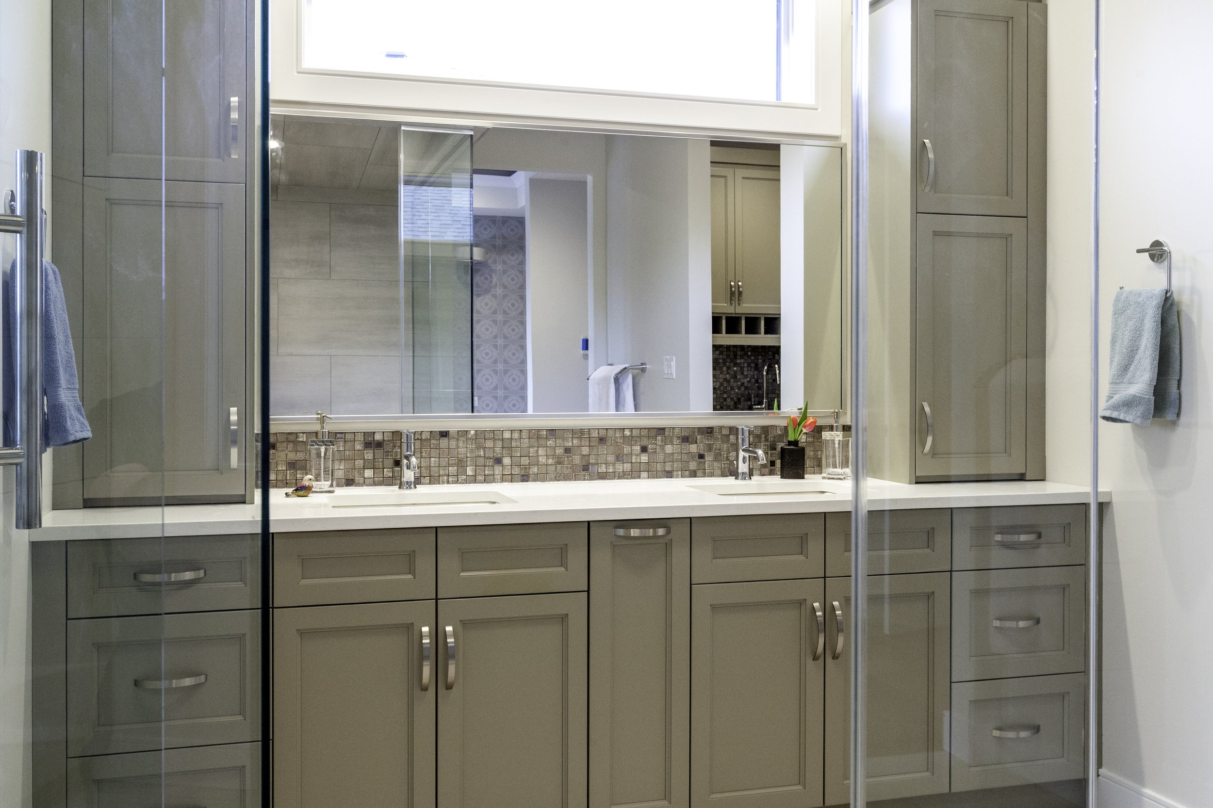Ensuite vanity with grey cabinets and quartz counters.
