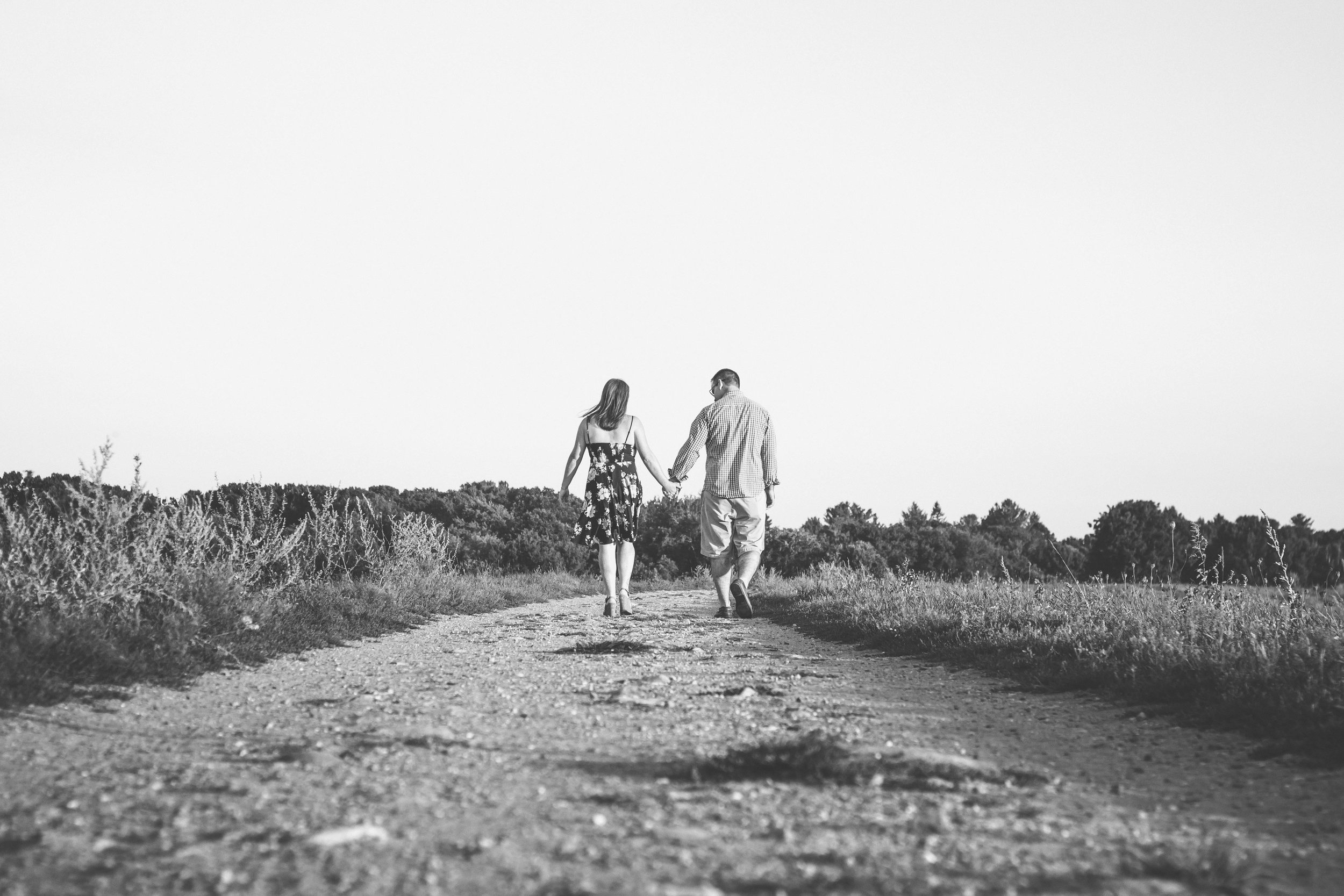 couple walking along path at sunset in black and white