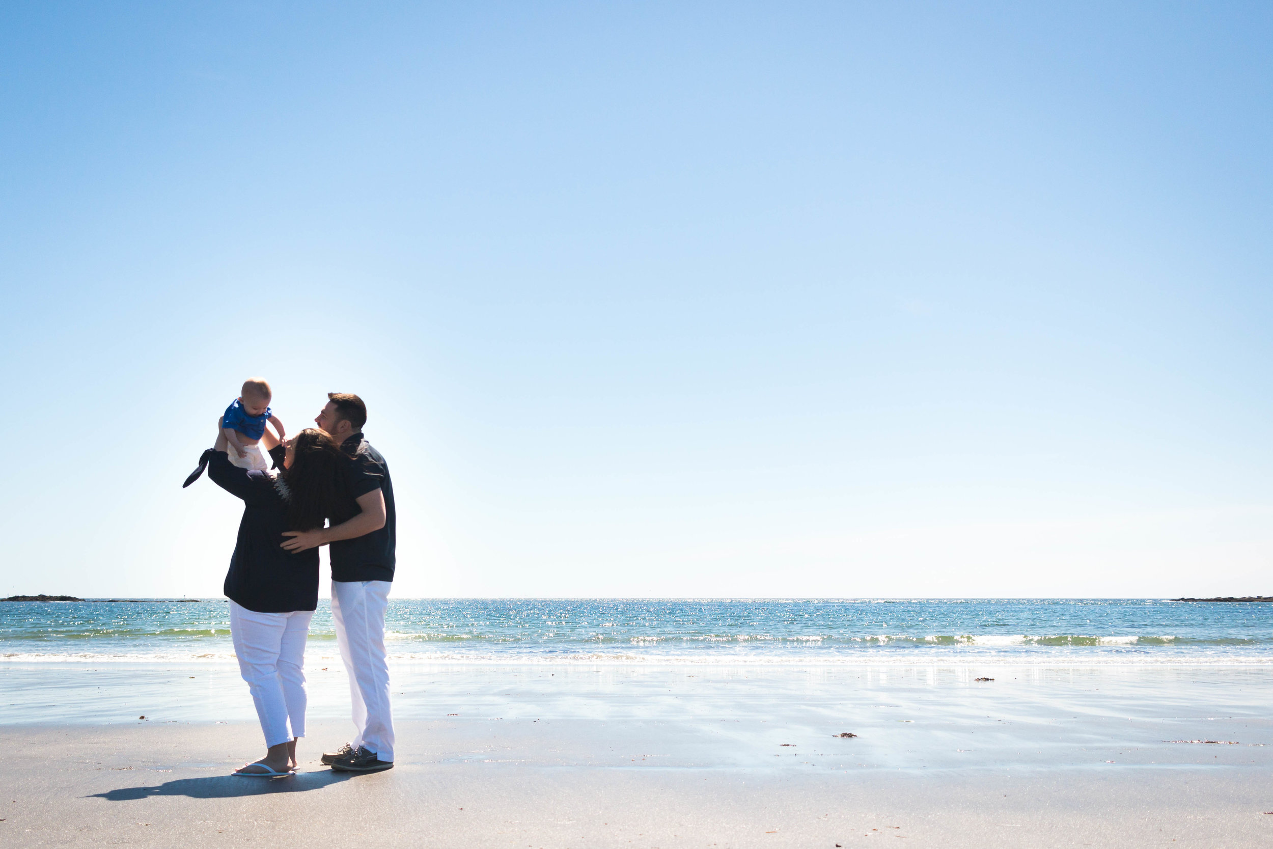 mom and dad holding baby on the beach