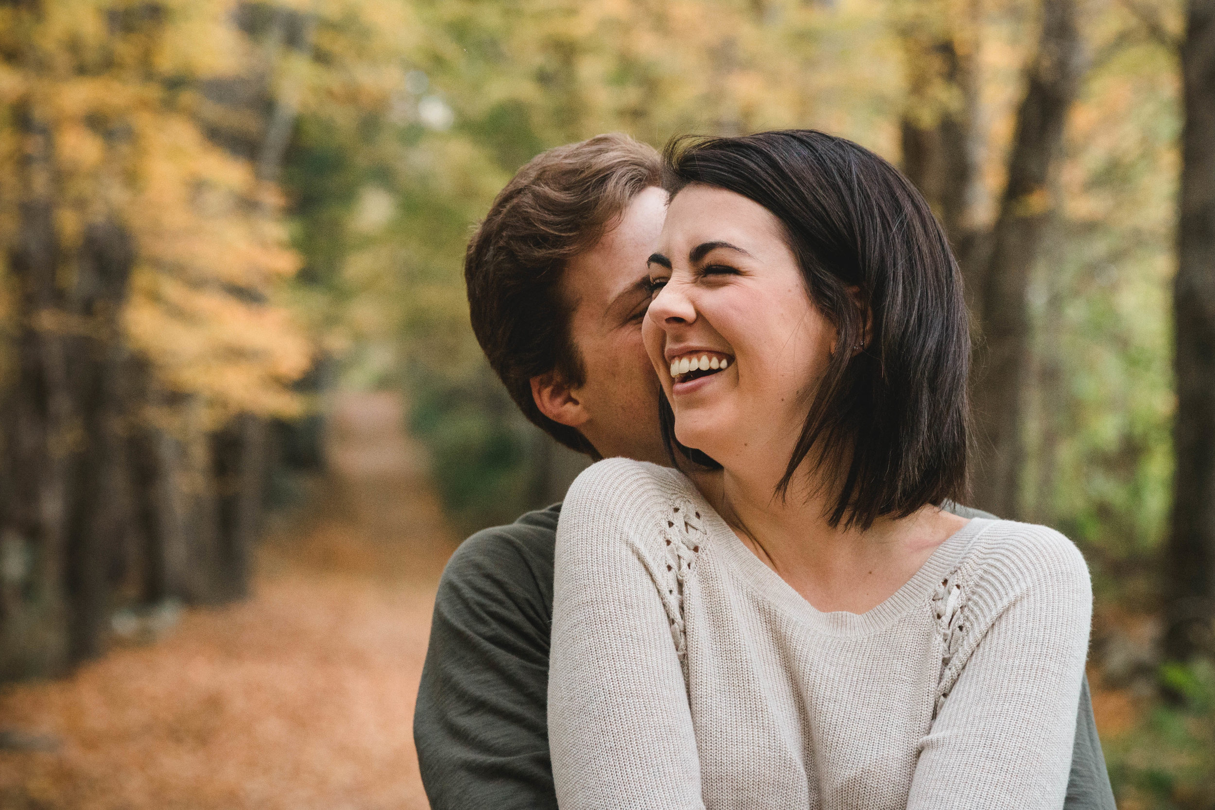 couple snuggling in New England fall foliage