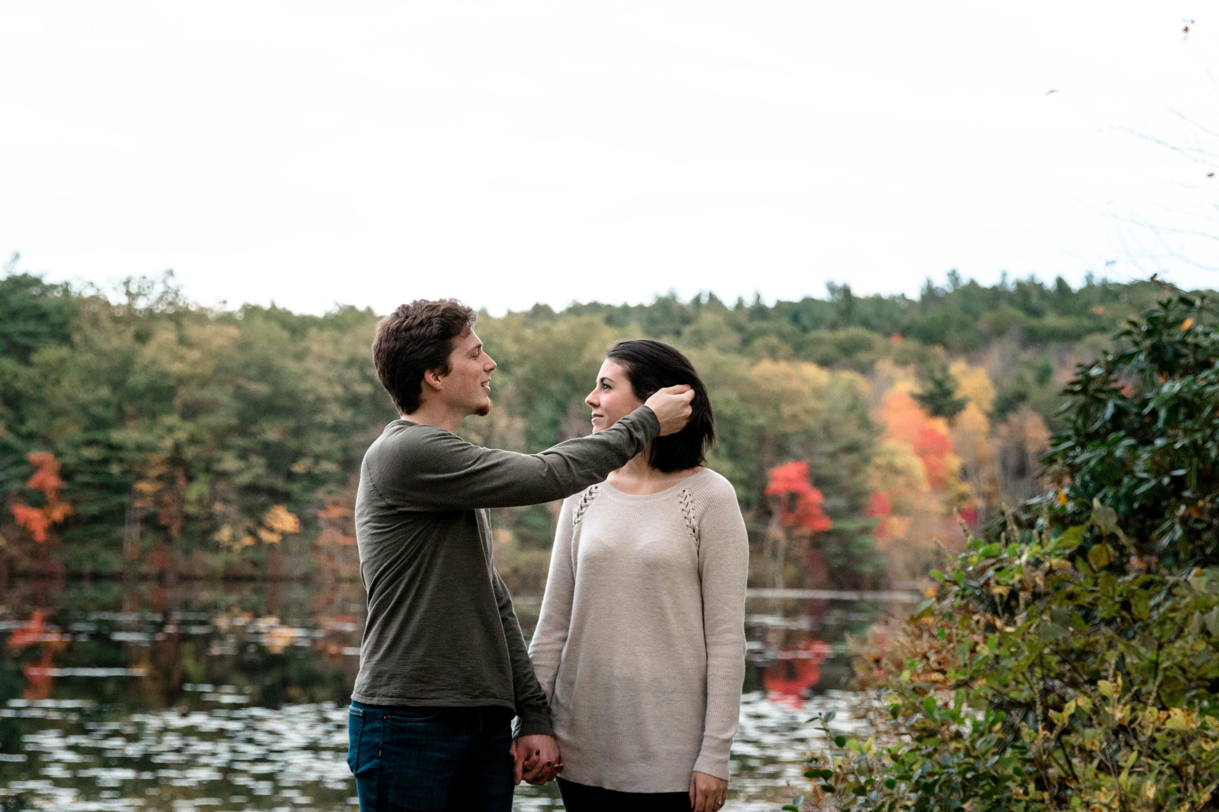 couple holding hands in front of fall foliage