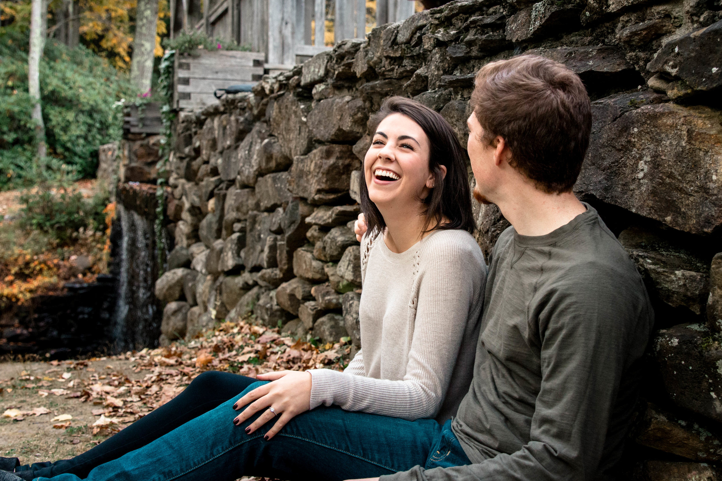 bride-to-be laughing with fiancé against rock wall and fall foliage