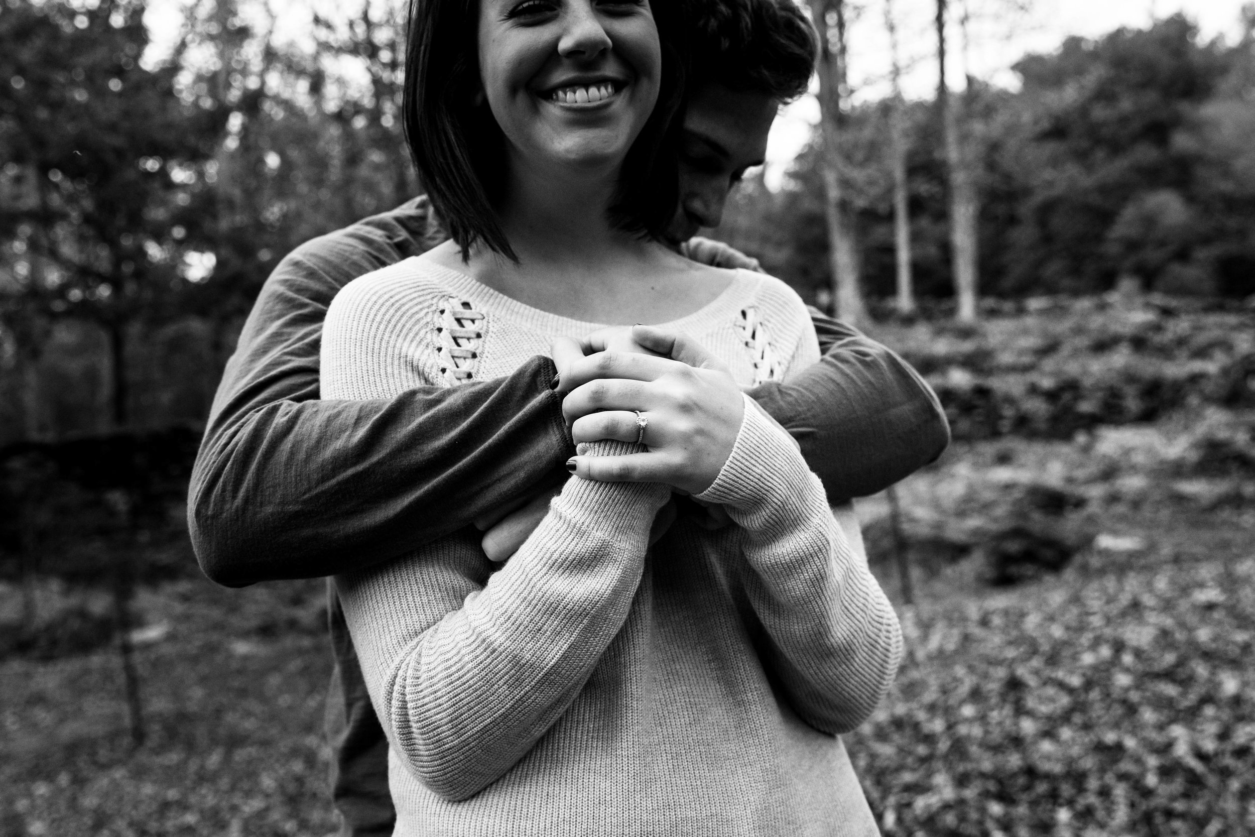 man hugs fiancé from behind in black and white
