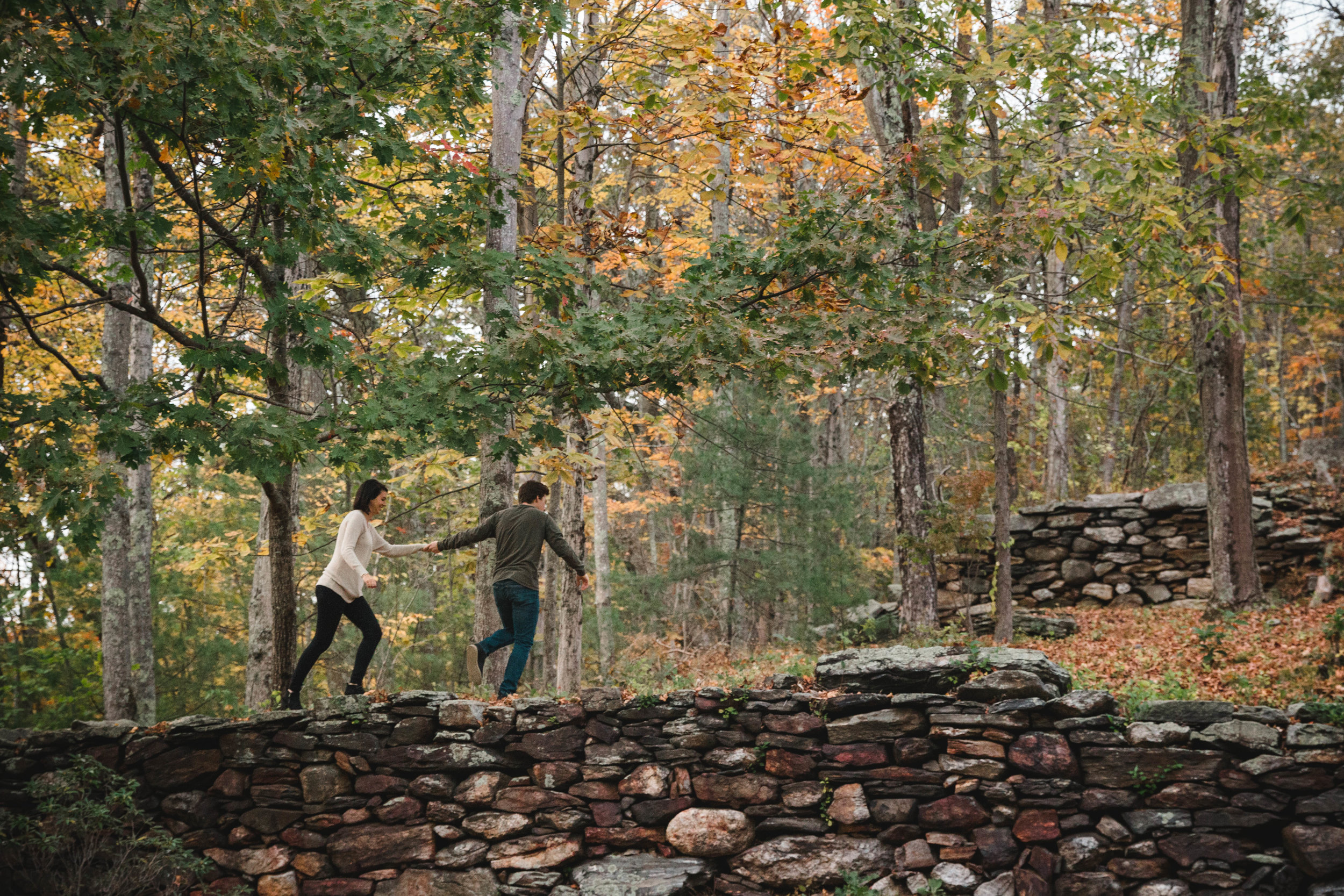 couple running into the woods with fall foliage