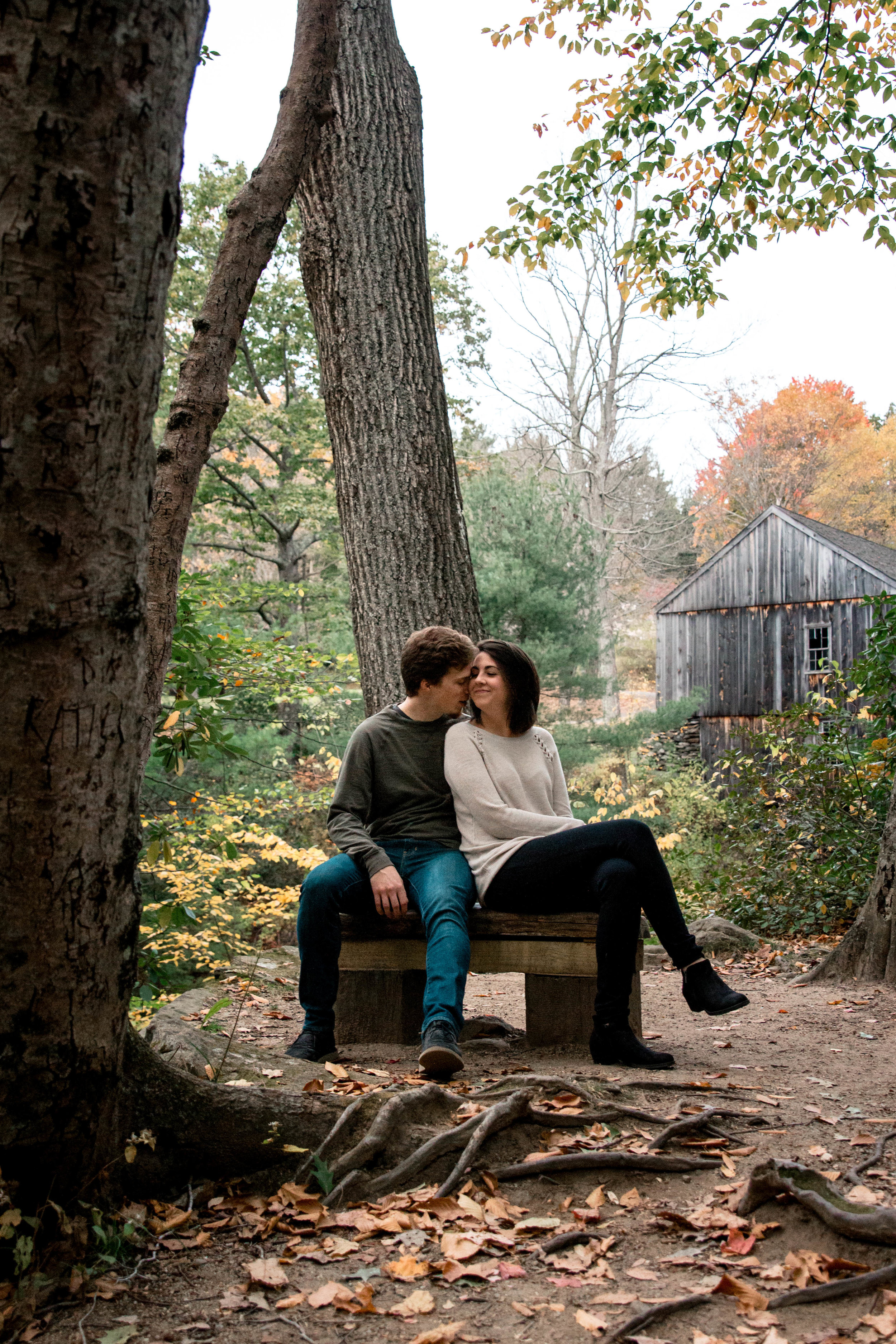 couple sitting on bench surrounded by fall foliage and wooden barn