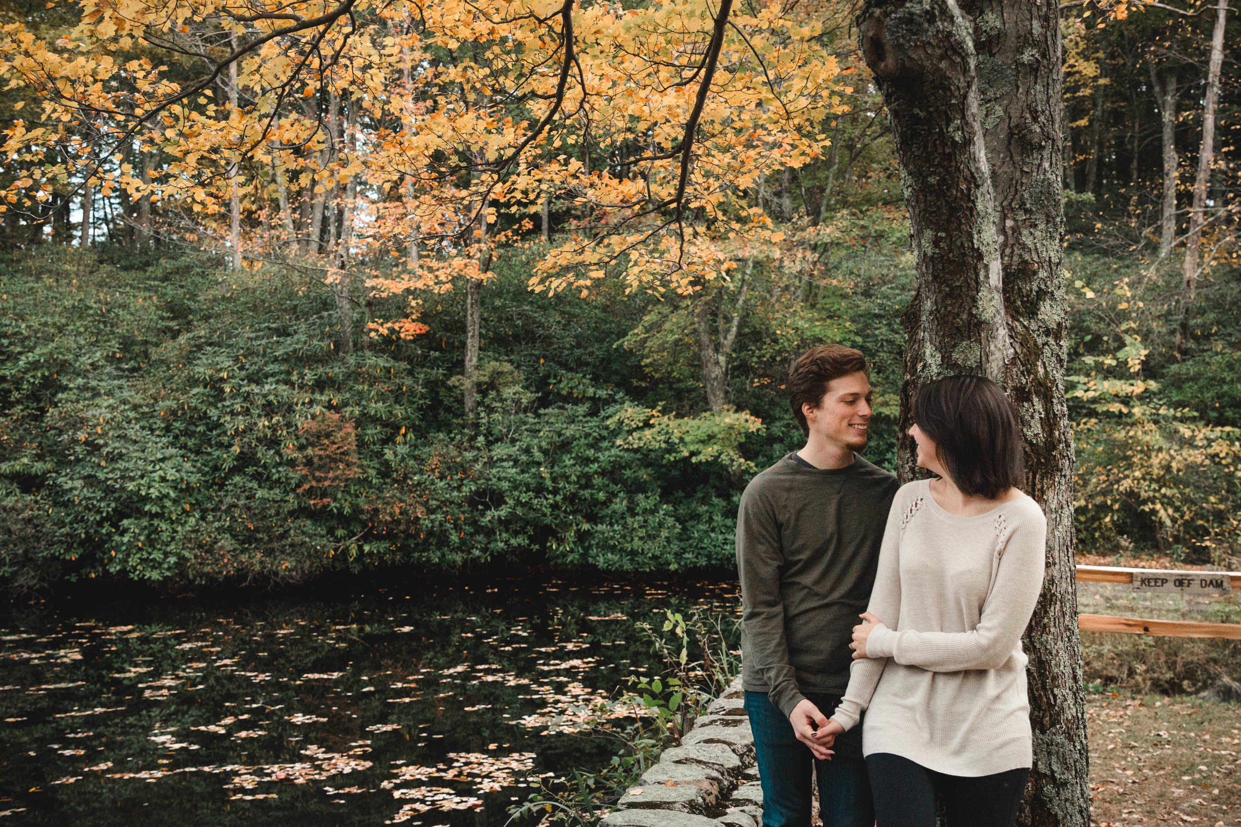 couple leaning on tree with yellow leaves