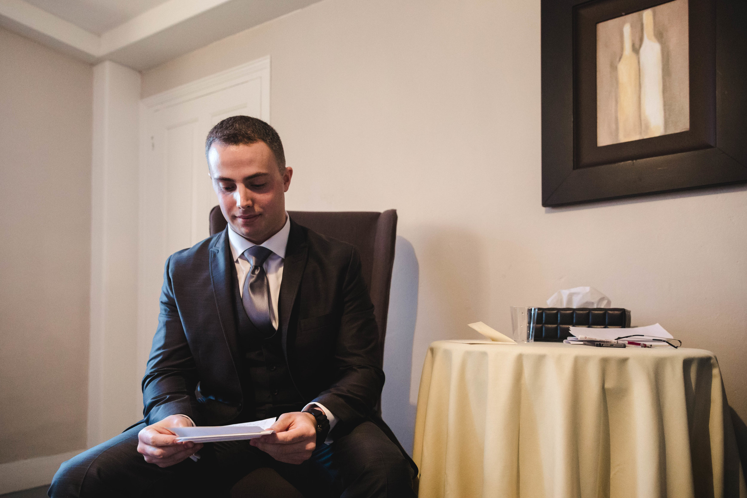 groom reading letter from bride before ceremony