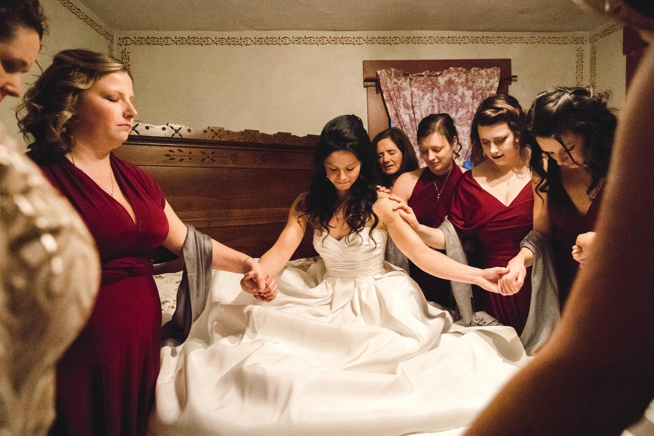 bride praying with bridesmaids before wedding ceremony