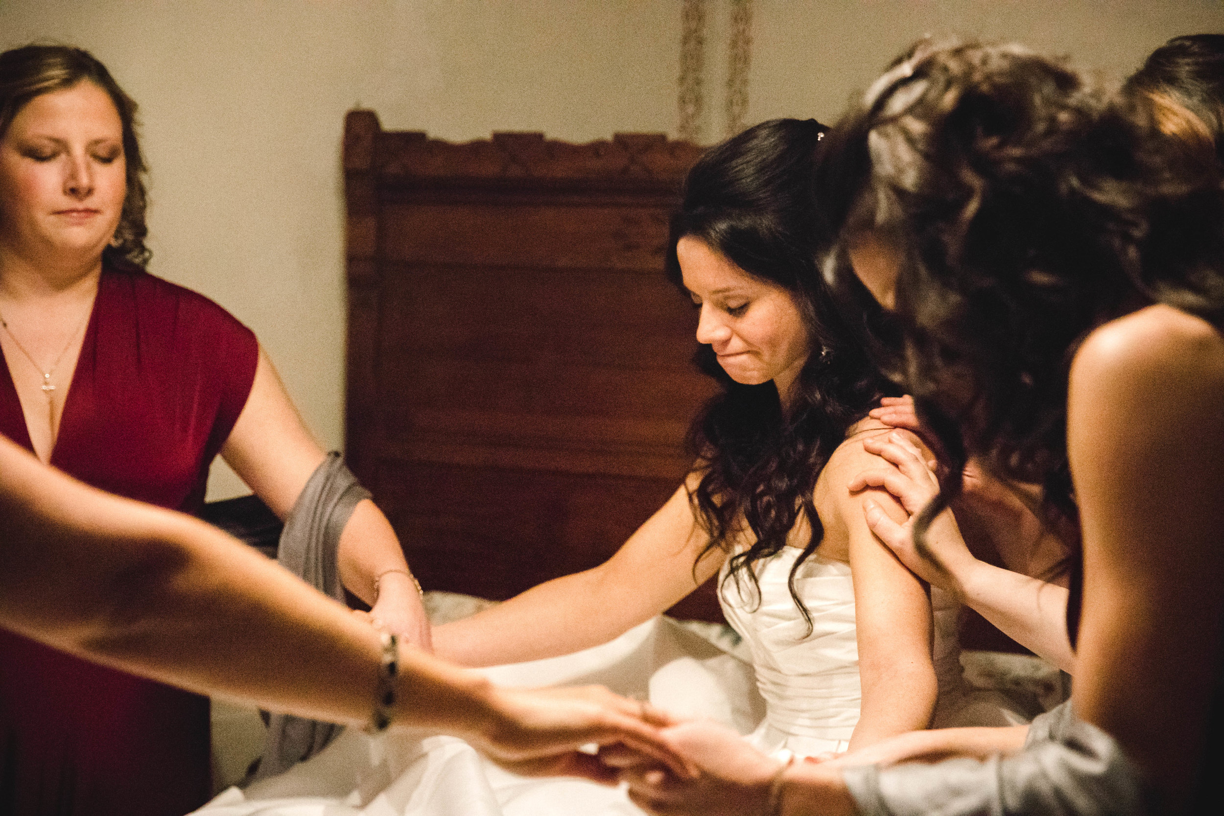 bride praying with bridal party