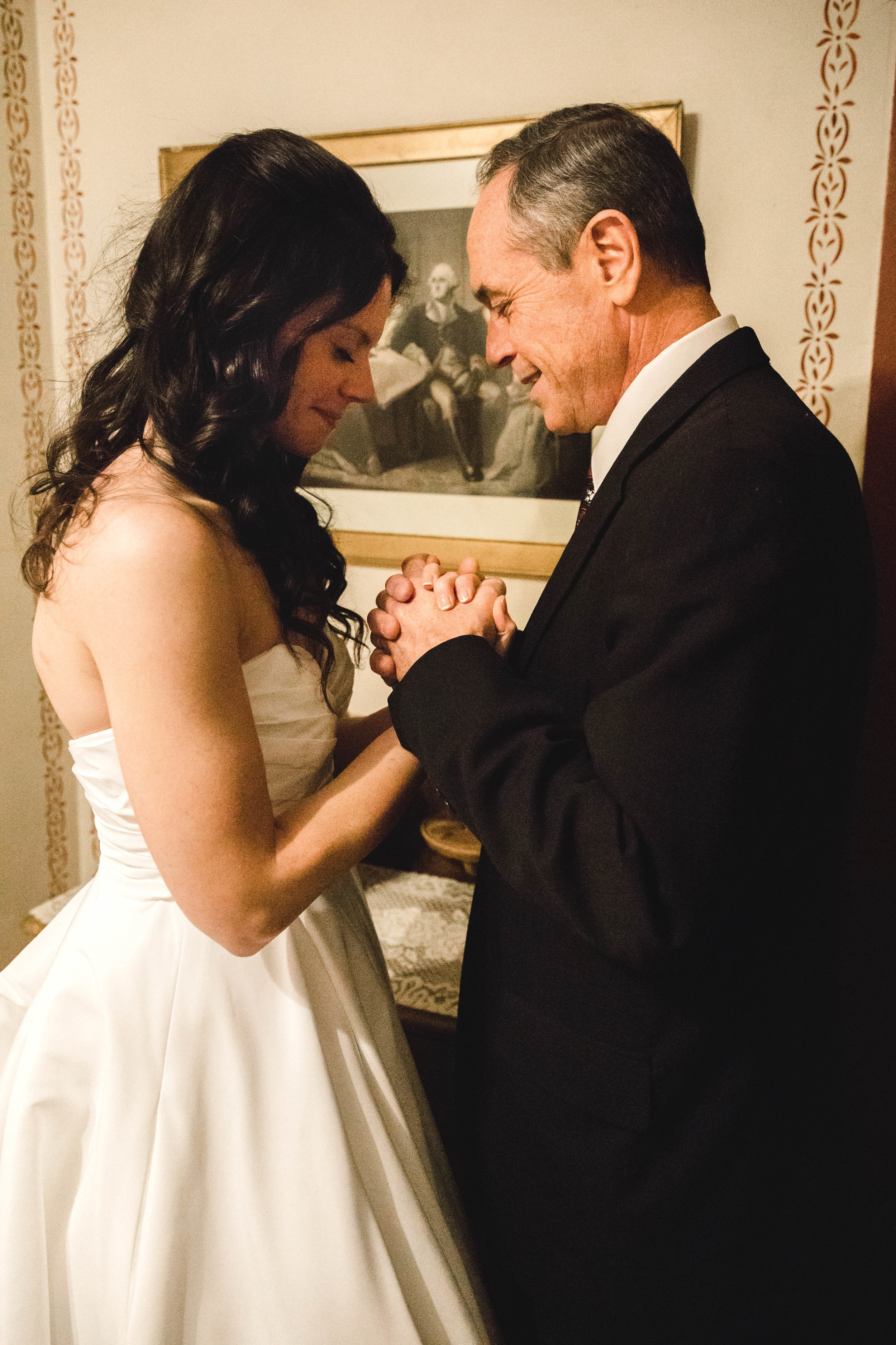 bride and father praying before wedding ceremony